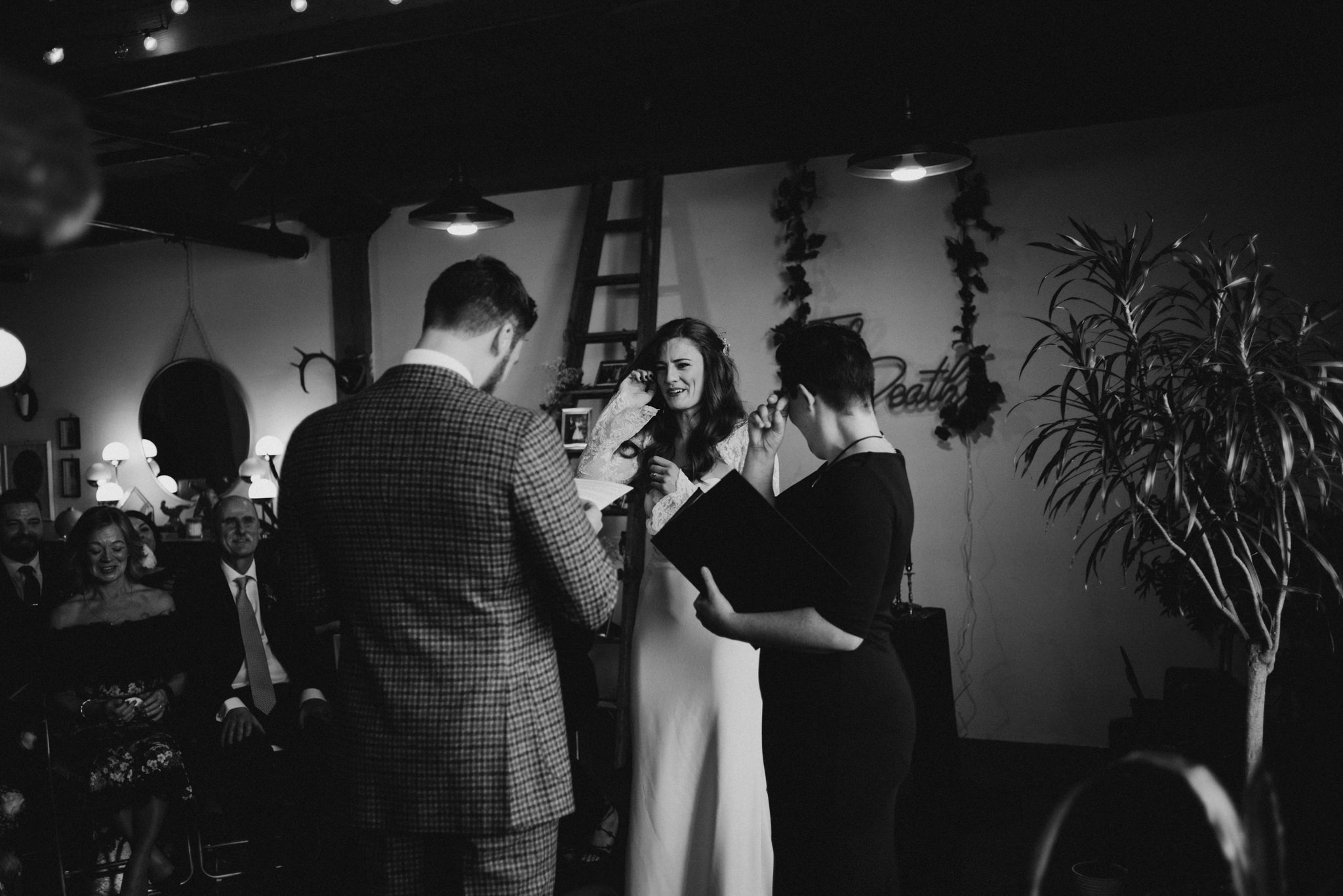 black and white image of bride and groom kissing during wedding ceremony in loft in Toronto