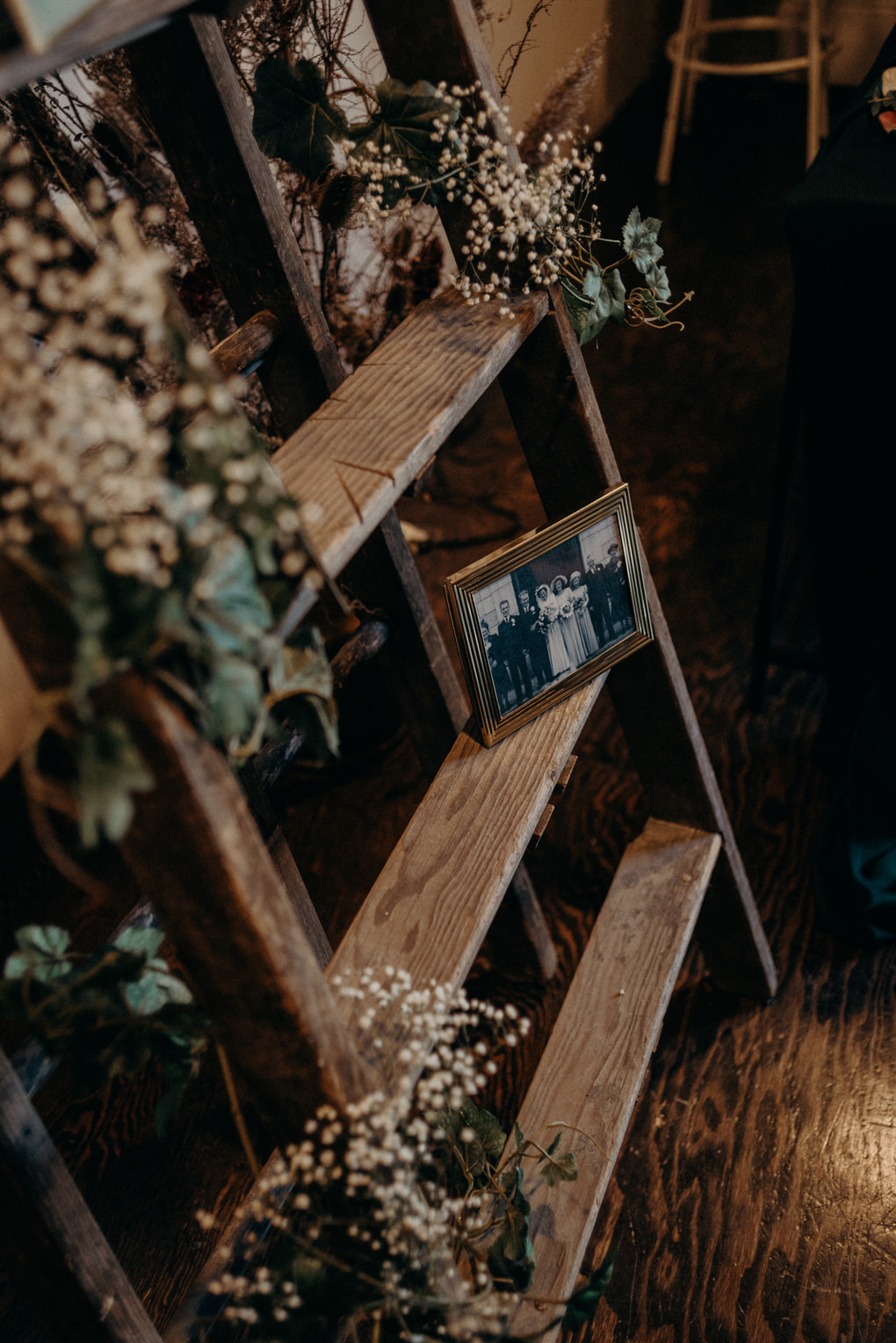 vintage family wedding portraits in frames on ladder