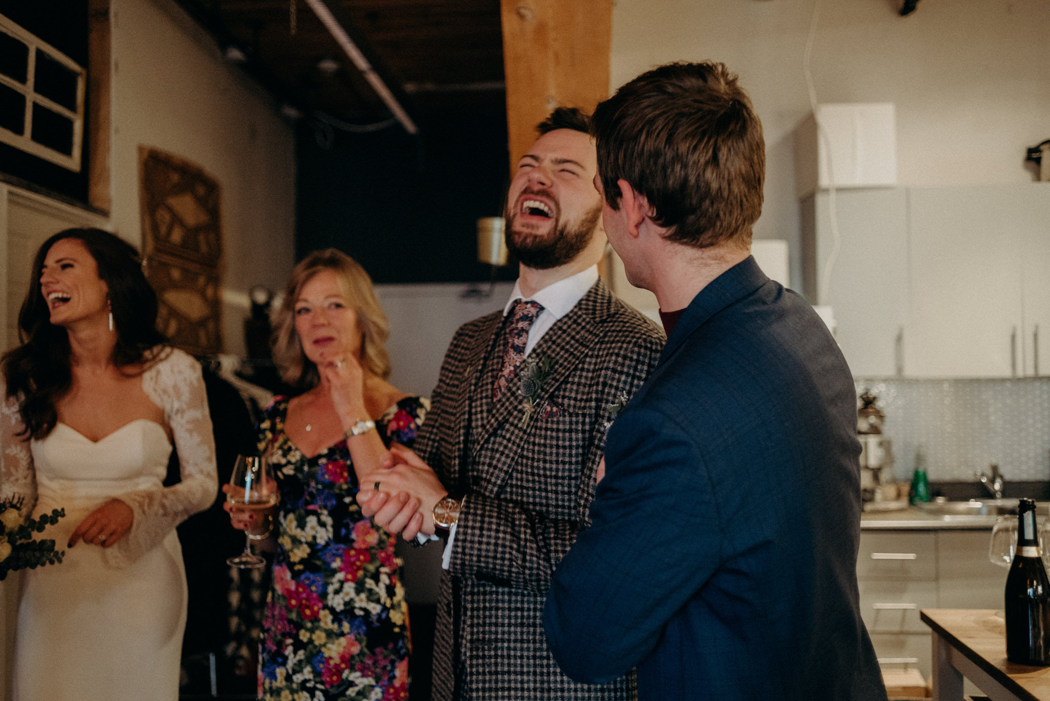 guests laughing with couple in loft wedding reception