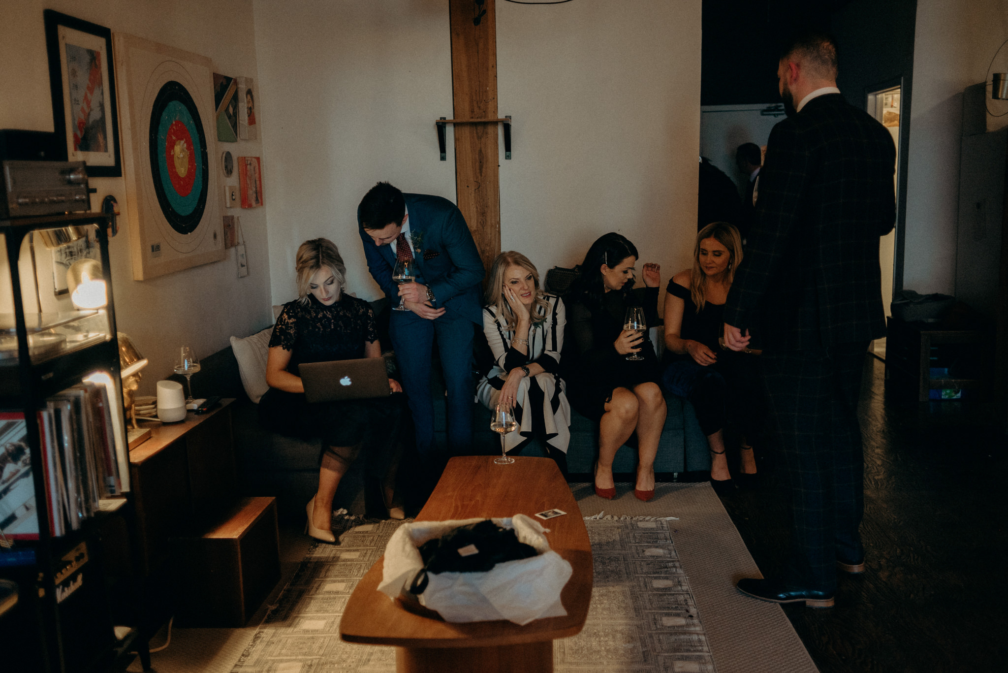 guests sitting on couch during cocktail hour in loft wedding reception