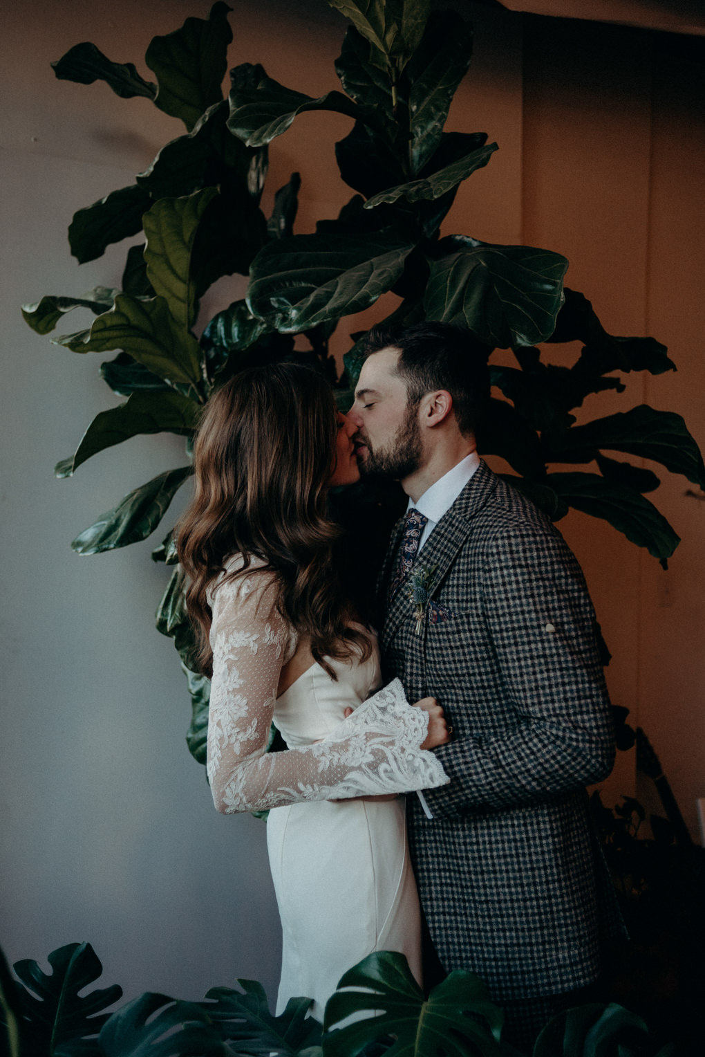 couple kissing in front of large fiddle fig tree