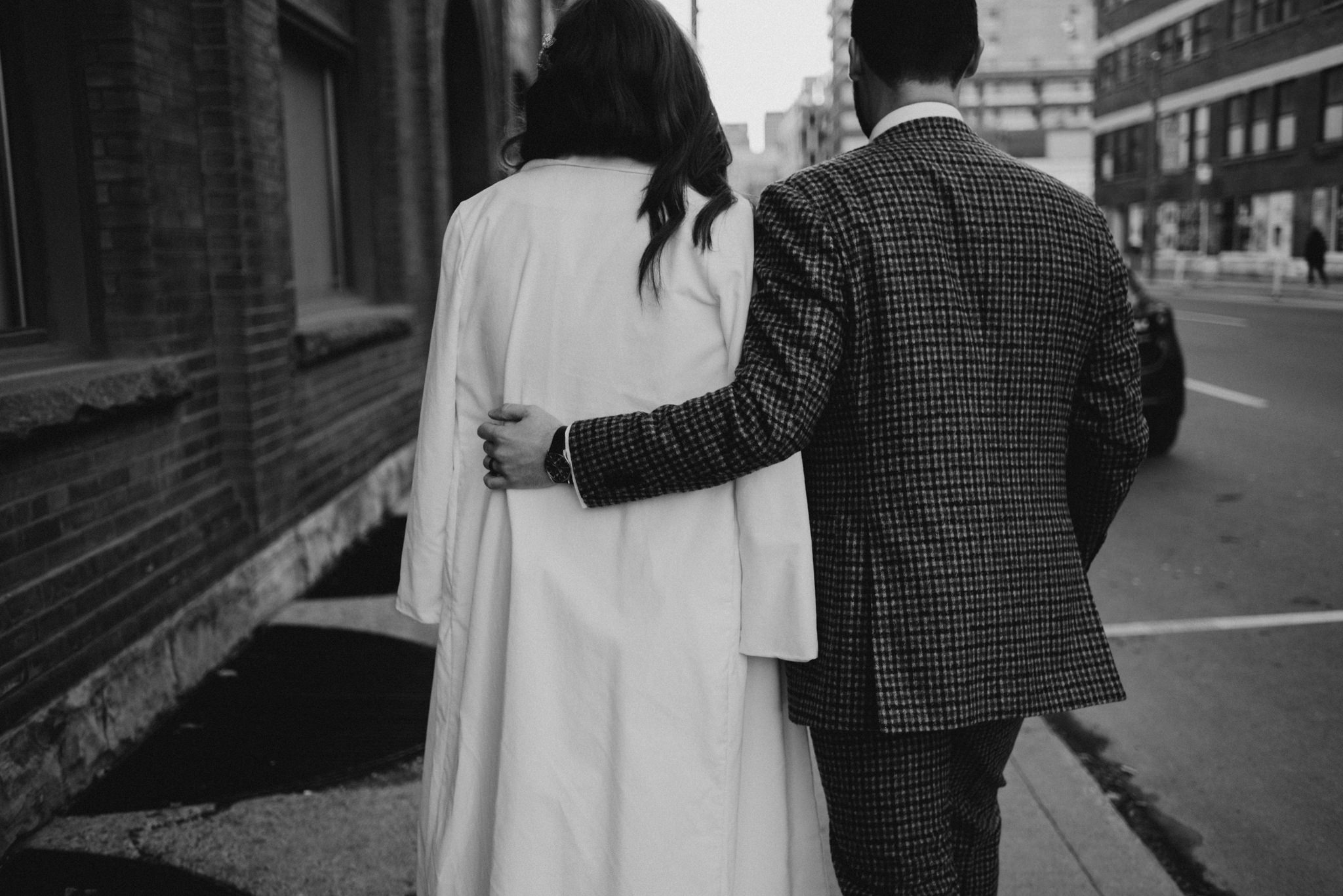 groom with arm around bride as they walk on sidewalk in downtown Toronto
