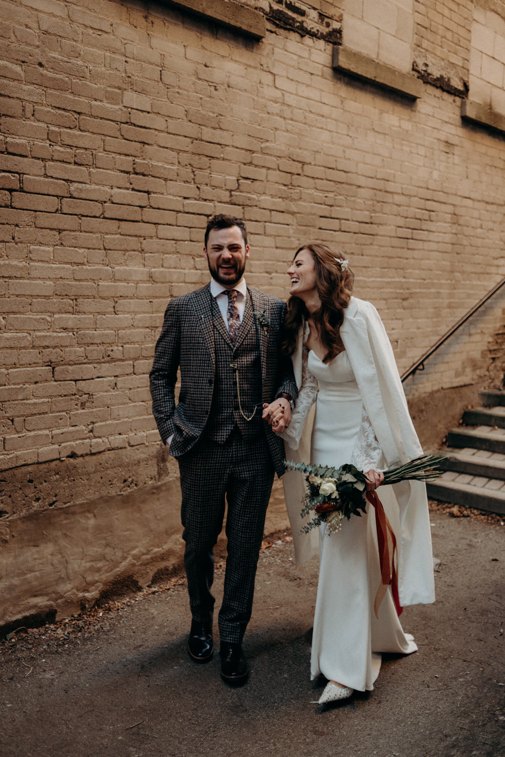 bride and groom walking and laughing in alleyway in Toronto