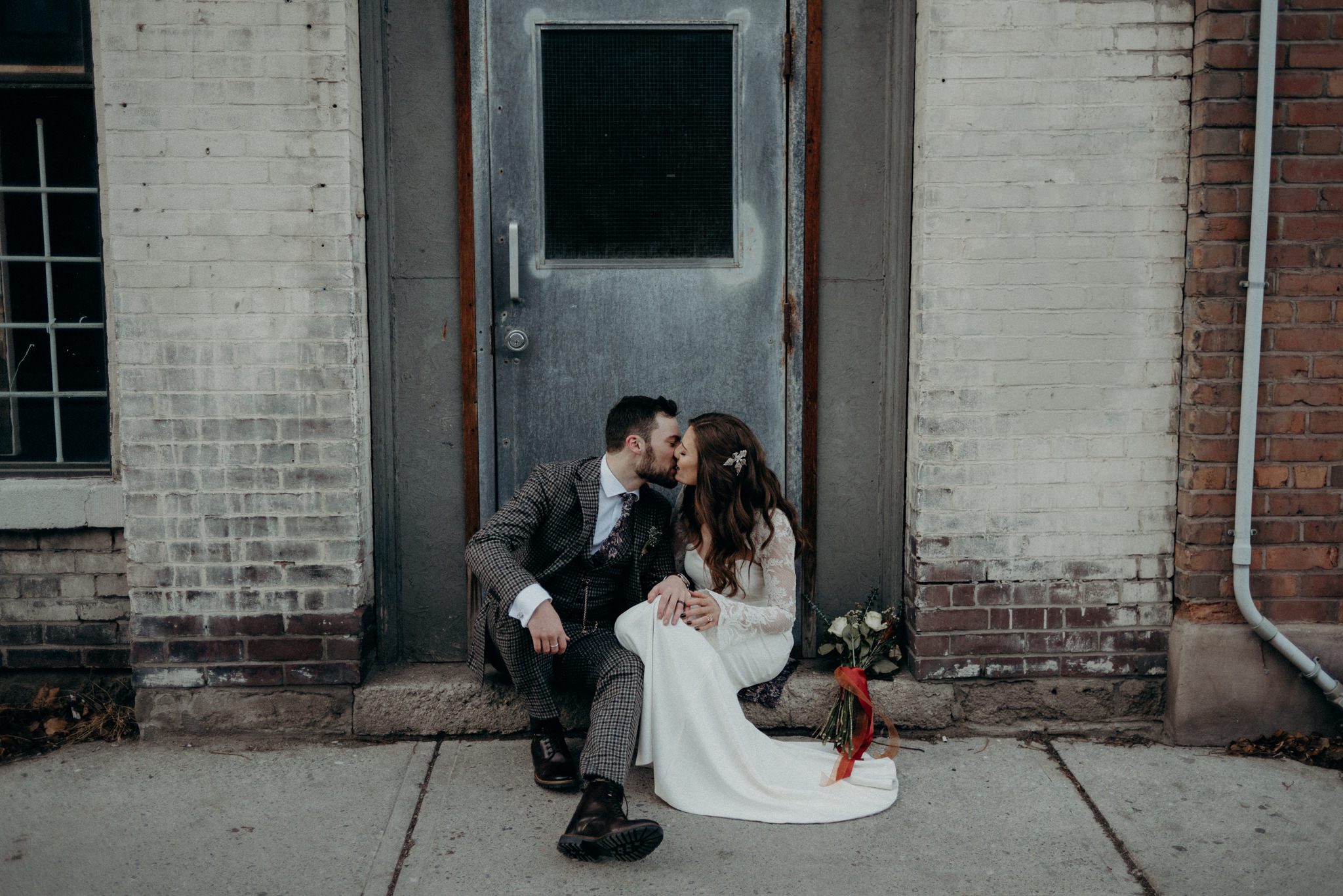bride and groom sitting on doorstep kissing