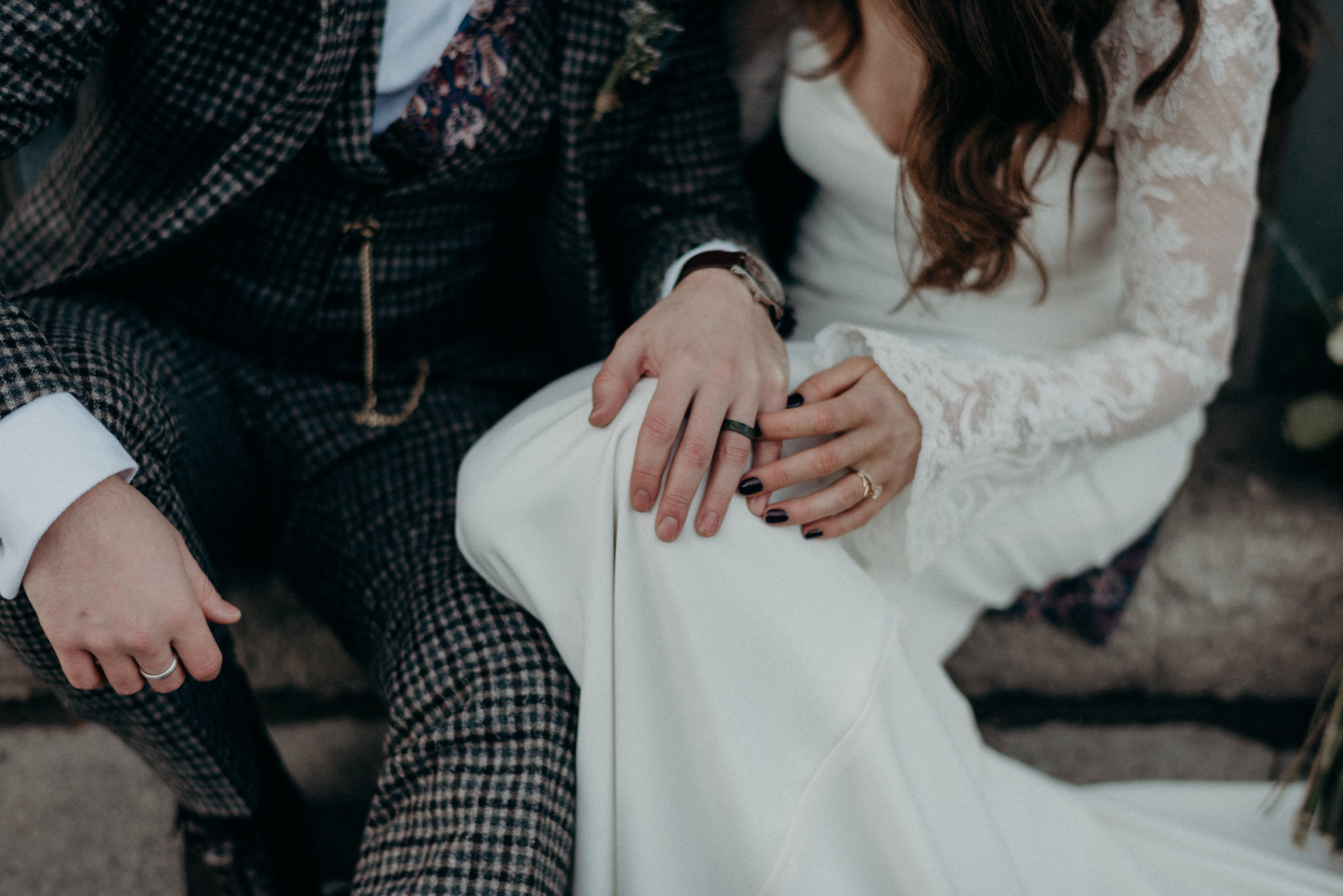 bride and groom sitting on ground holding hands