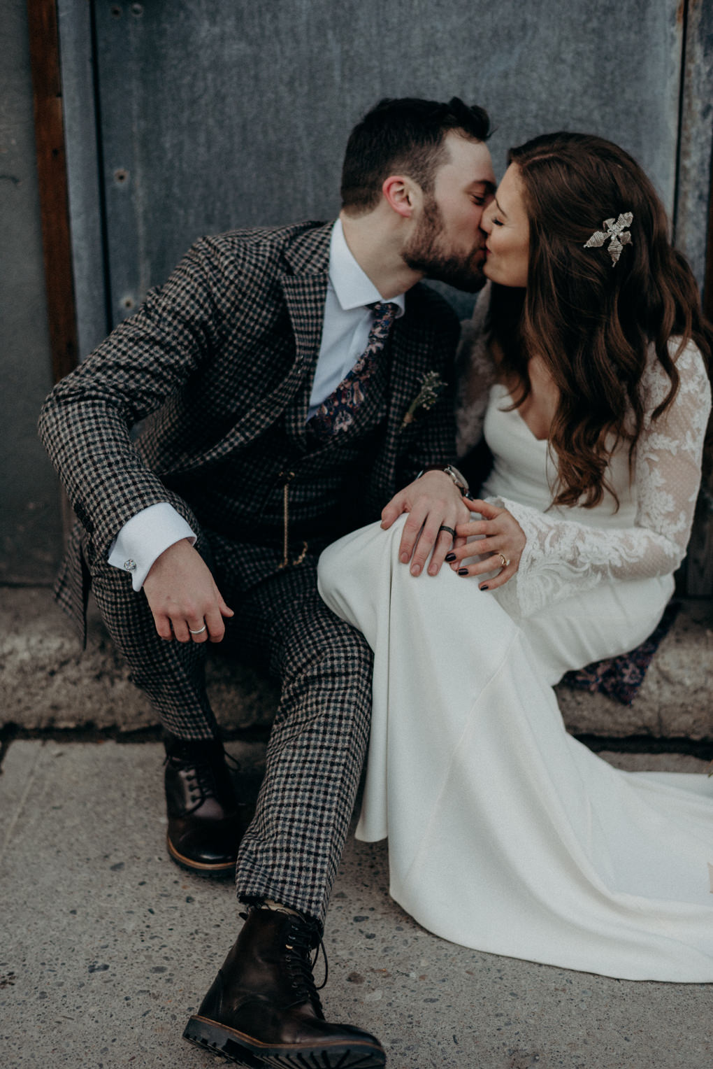 bride and groom kissing and sitting on doorstep on street