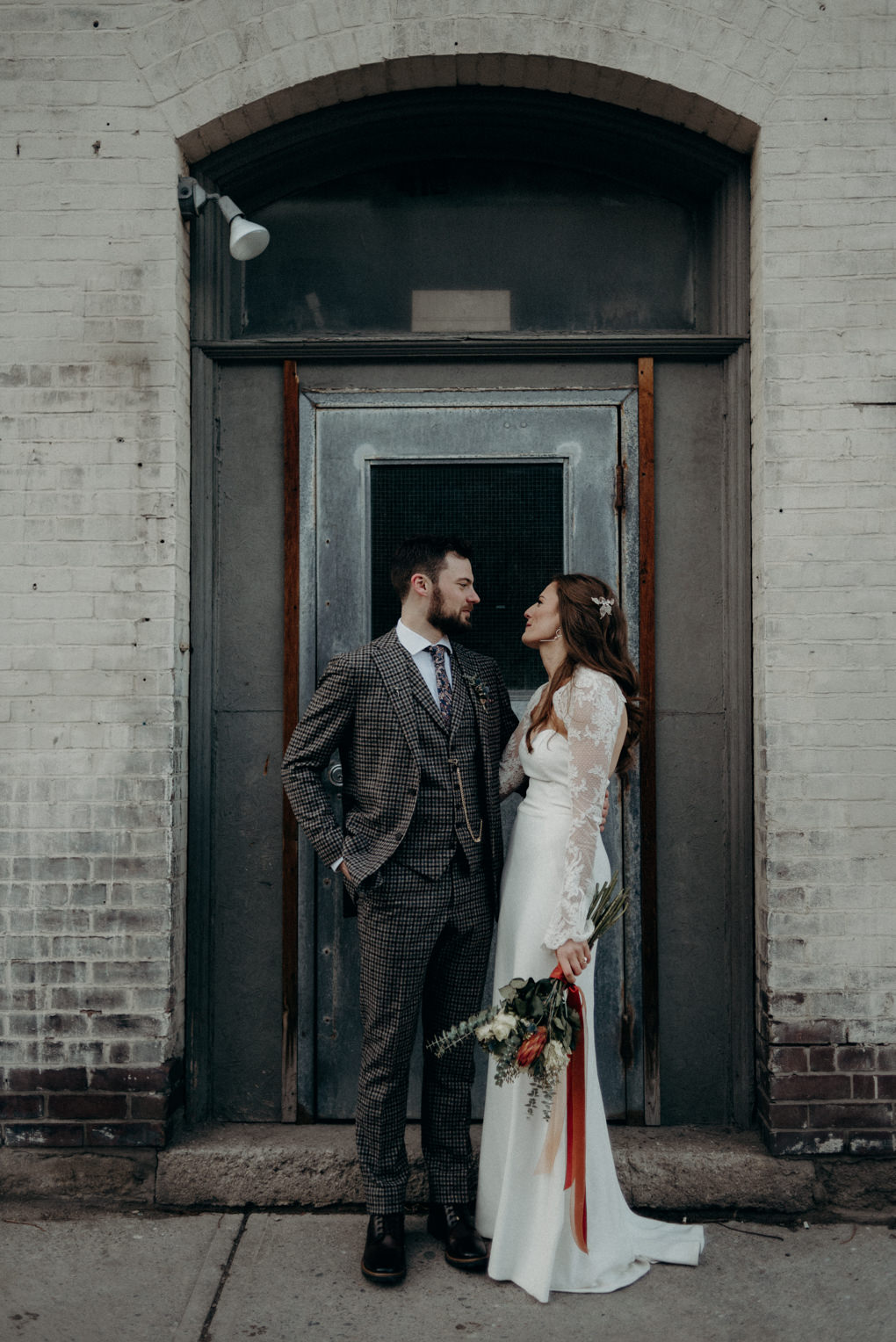 bride and groom standing in doorway of loft building