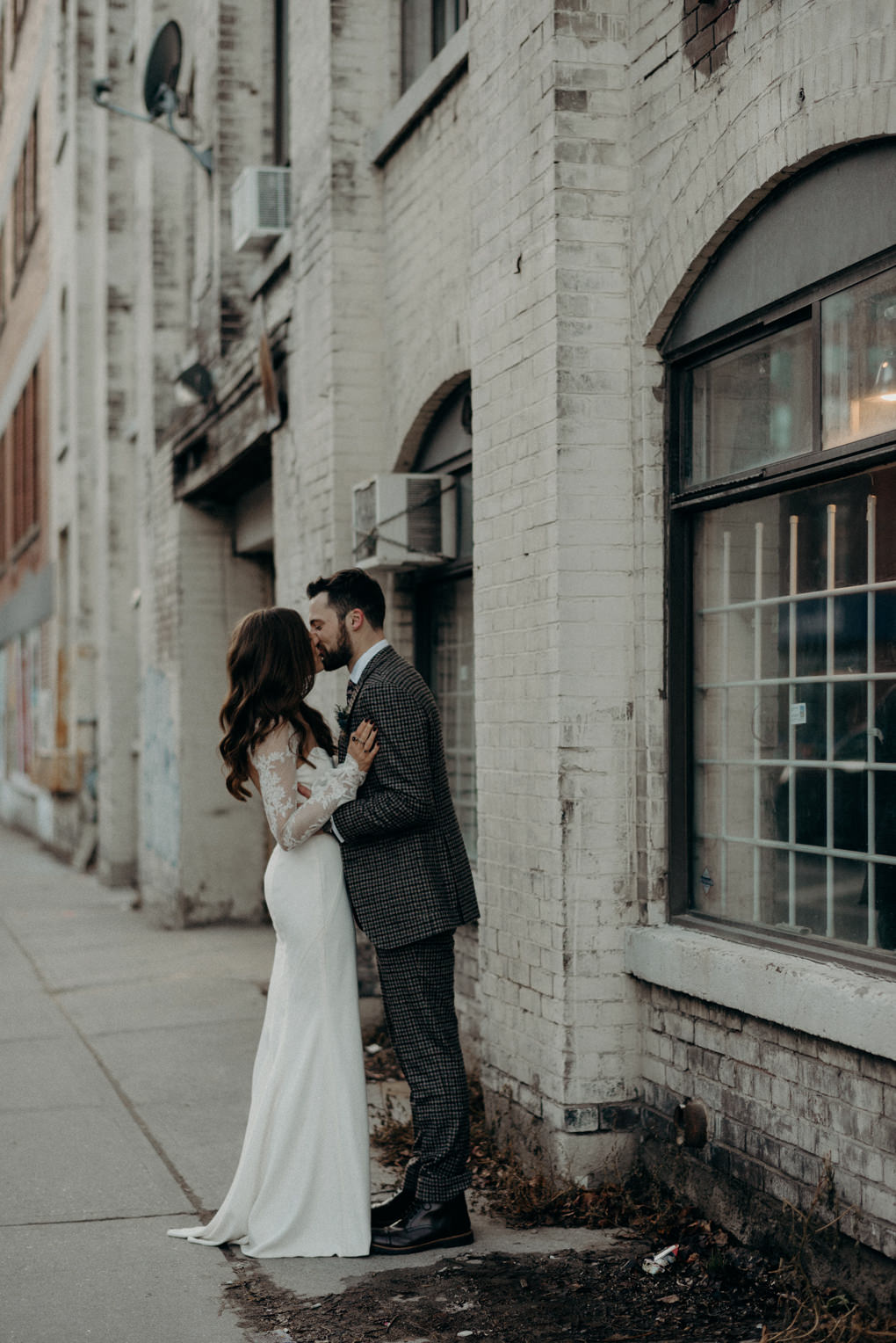 couple kissing on the sidewalk in front of old building