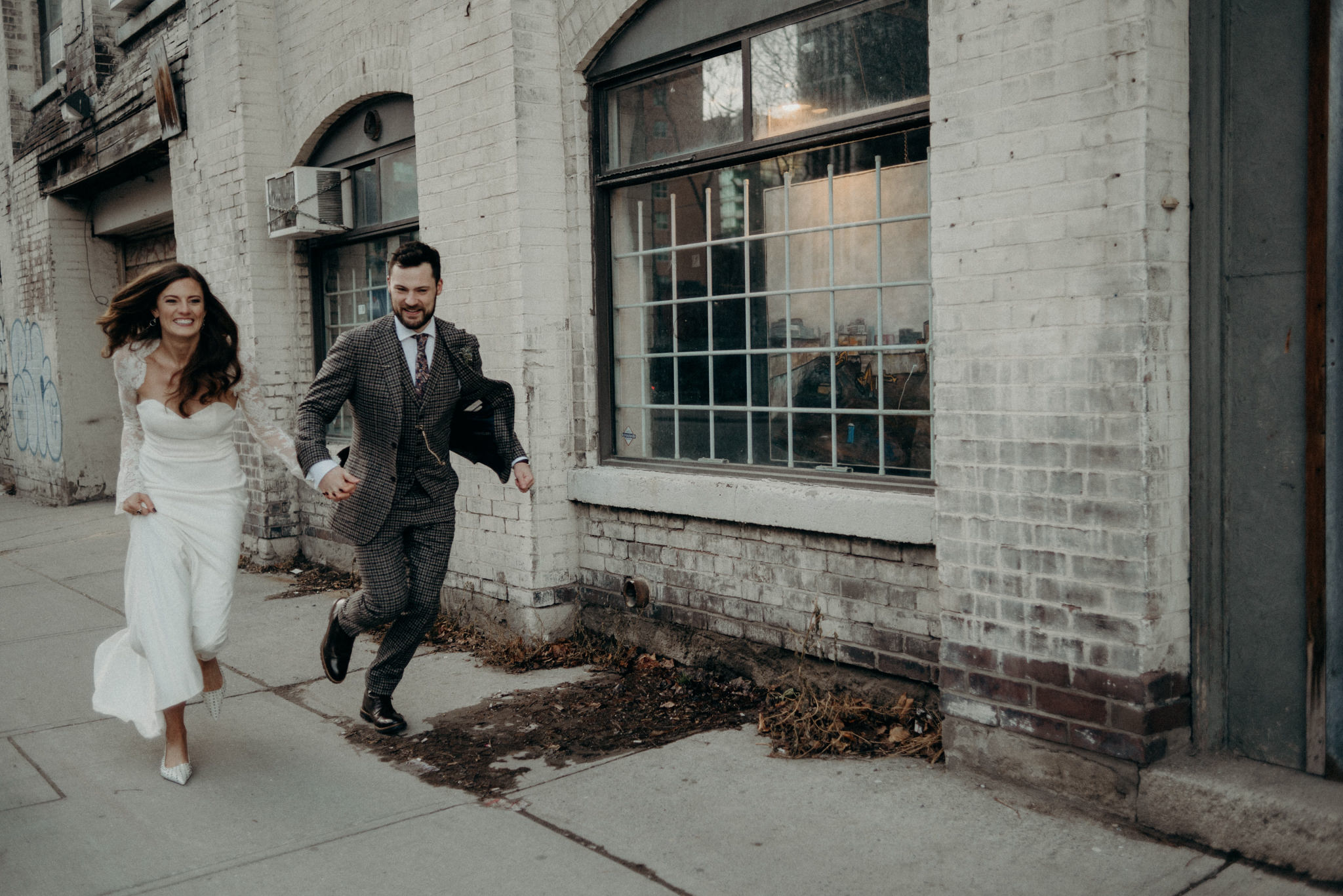 bride and groom running on sidewalk holding hands