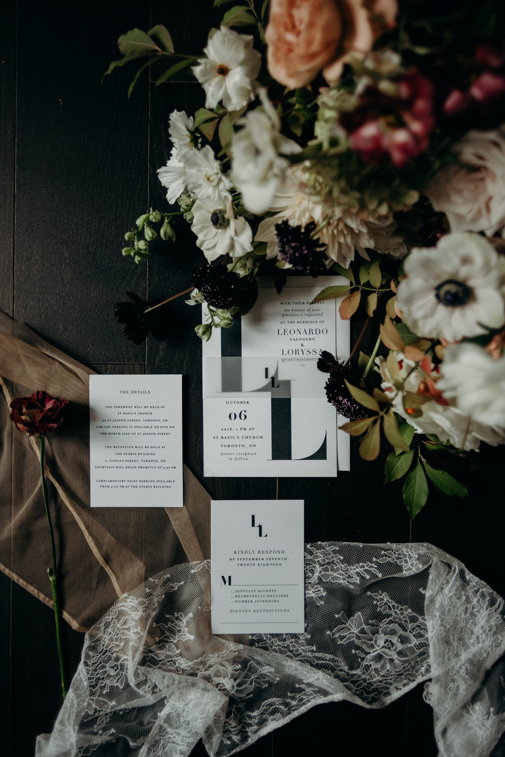 minimalist wedding invitation suite on dark floor surrounded by flowers and lace