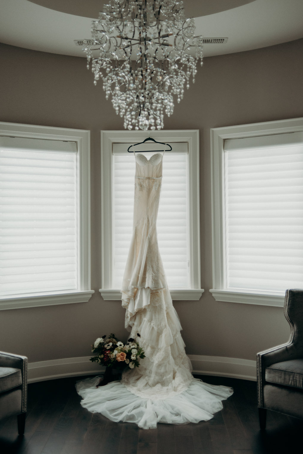 wedding dress with long train hanging in window