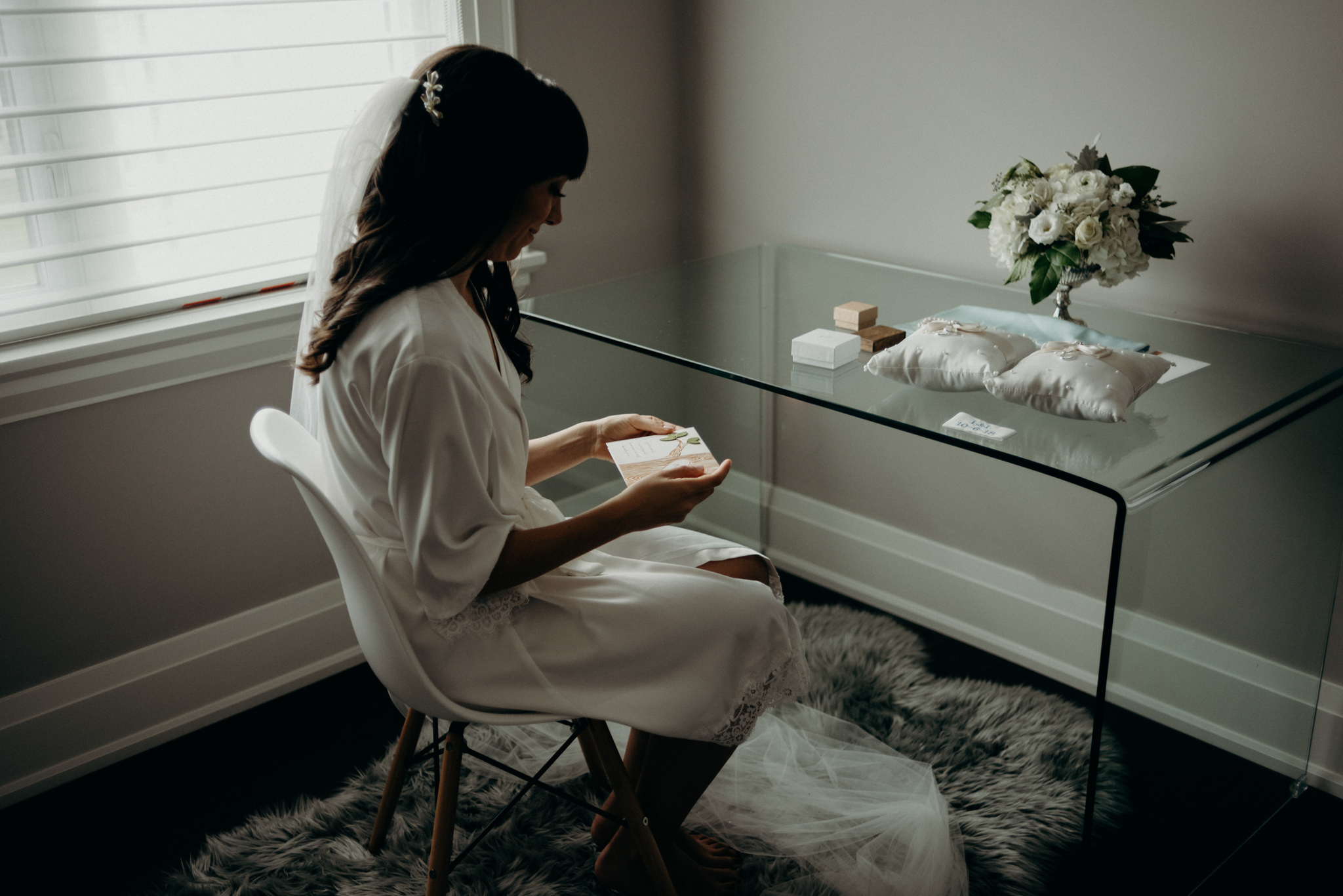bride sitting in chair reading card while getting ready