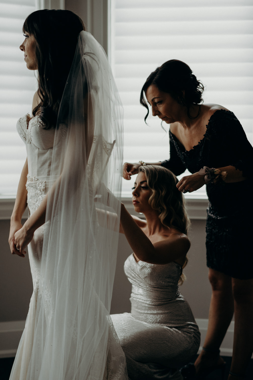 sister and mother of bride helping do up back of dress