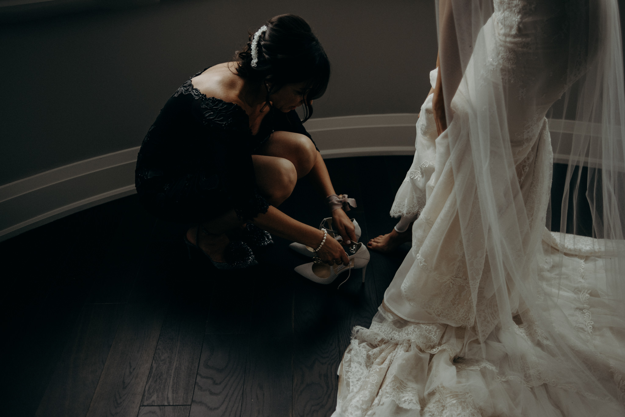 mother of bride putting on shoes for bride