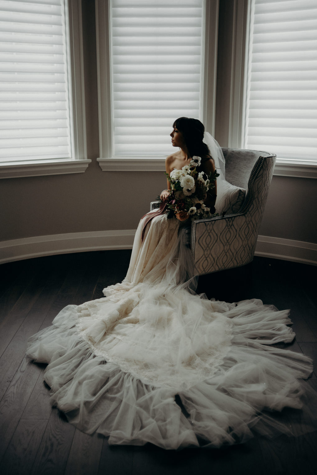 ethereal portraits of bride sitting in chair with bouquet