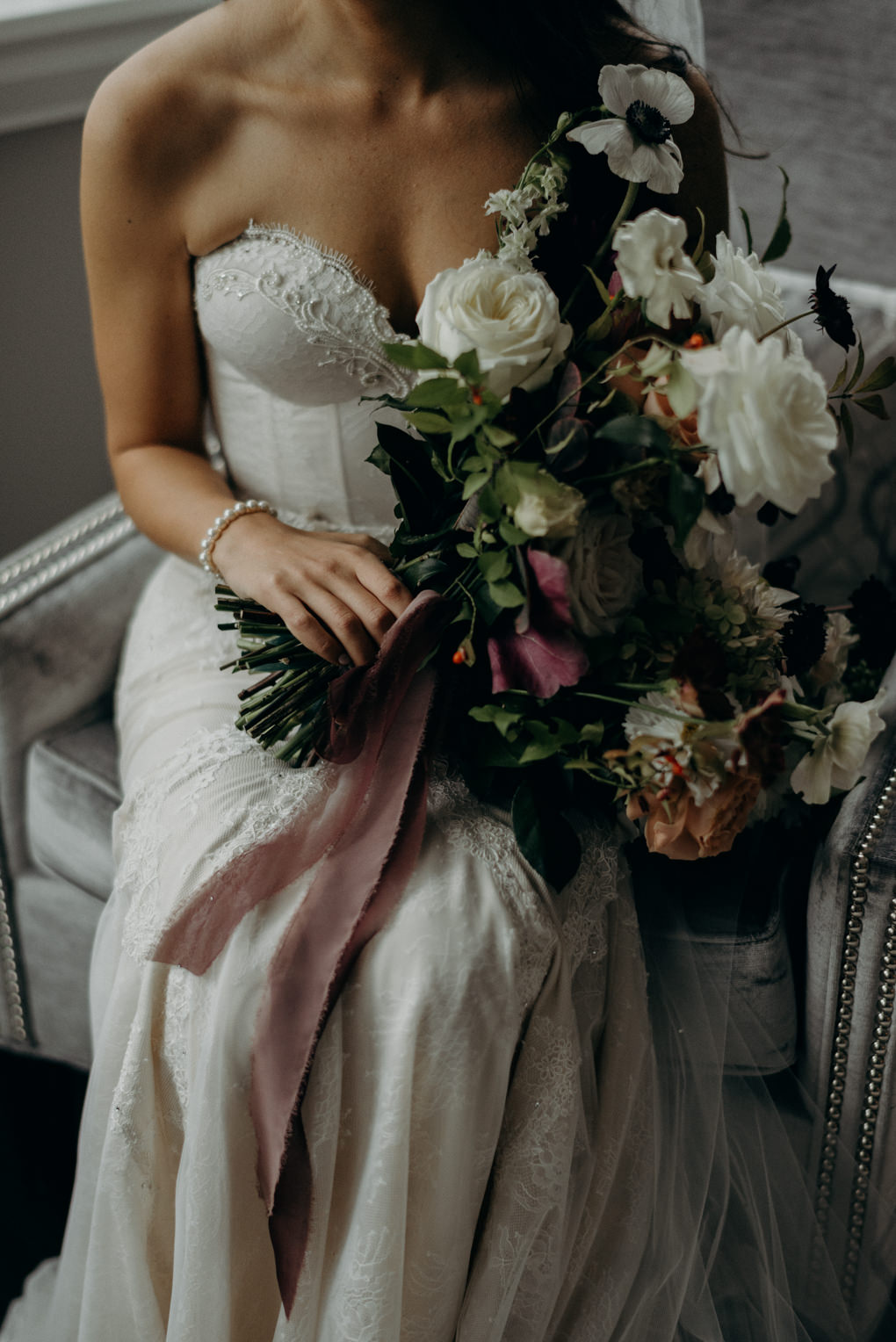 bride holding bouquet with lace ribbon
