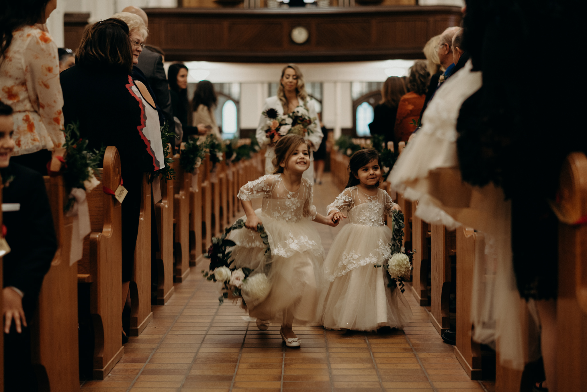 flower girls holding hands and running down aisle of church