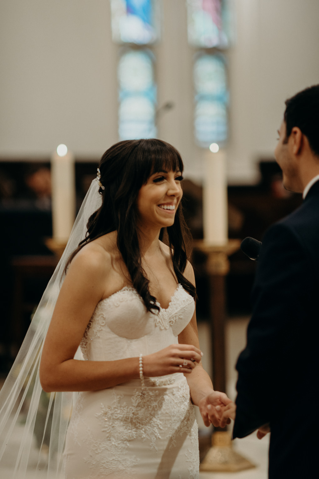 bride smiling while exchanging rings with groom
