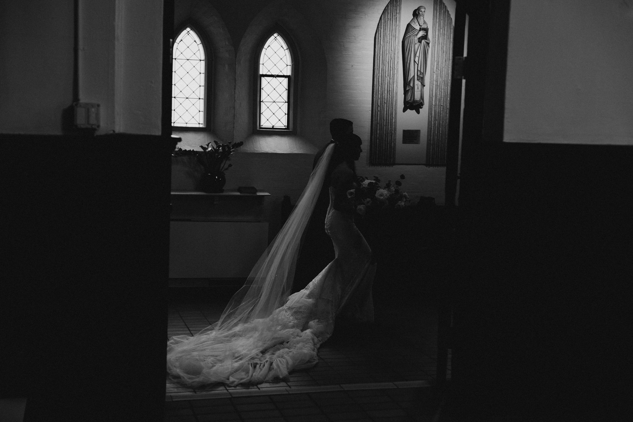 Black and white images of bride and groom walking in St Basil's church in Toronto