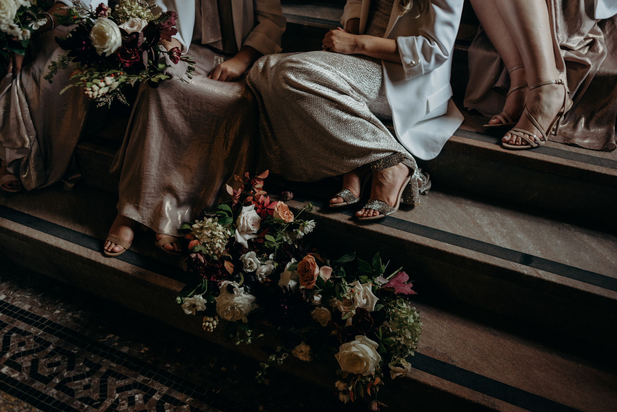 bridesmaids sitting on steps inside Knox College