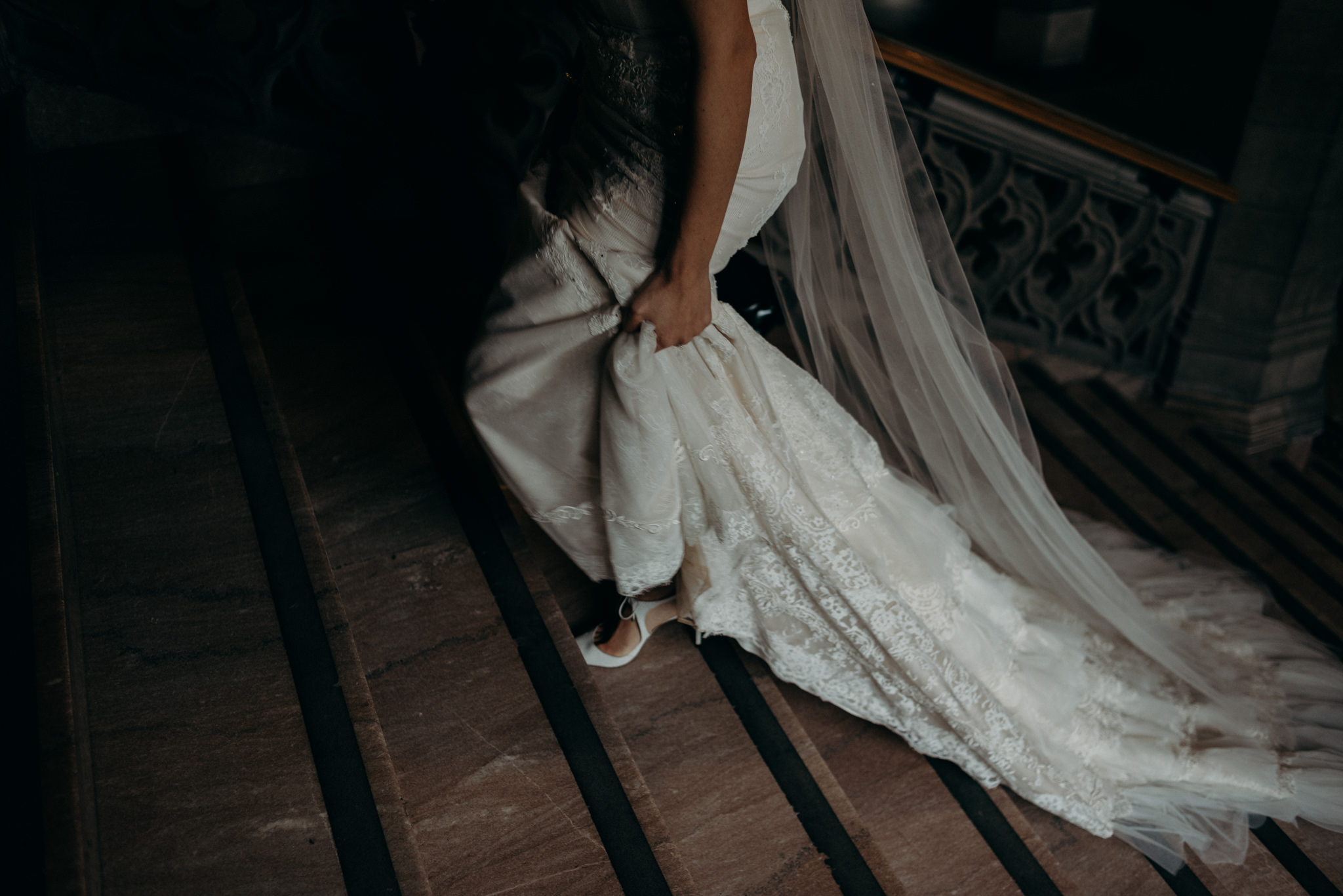 bride walking up stairs holding dress