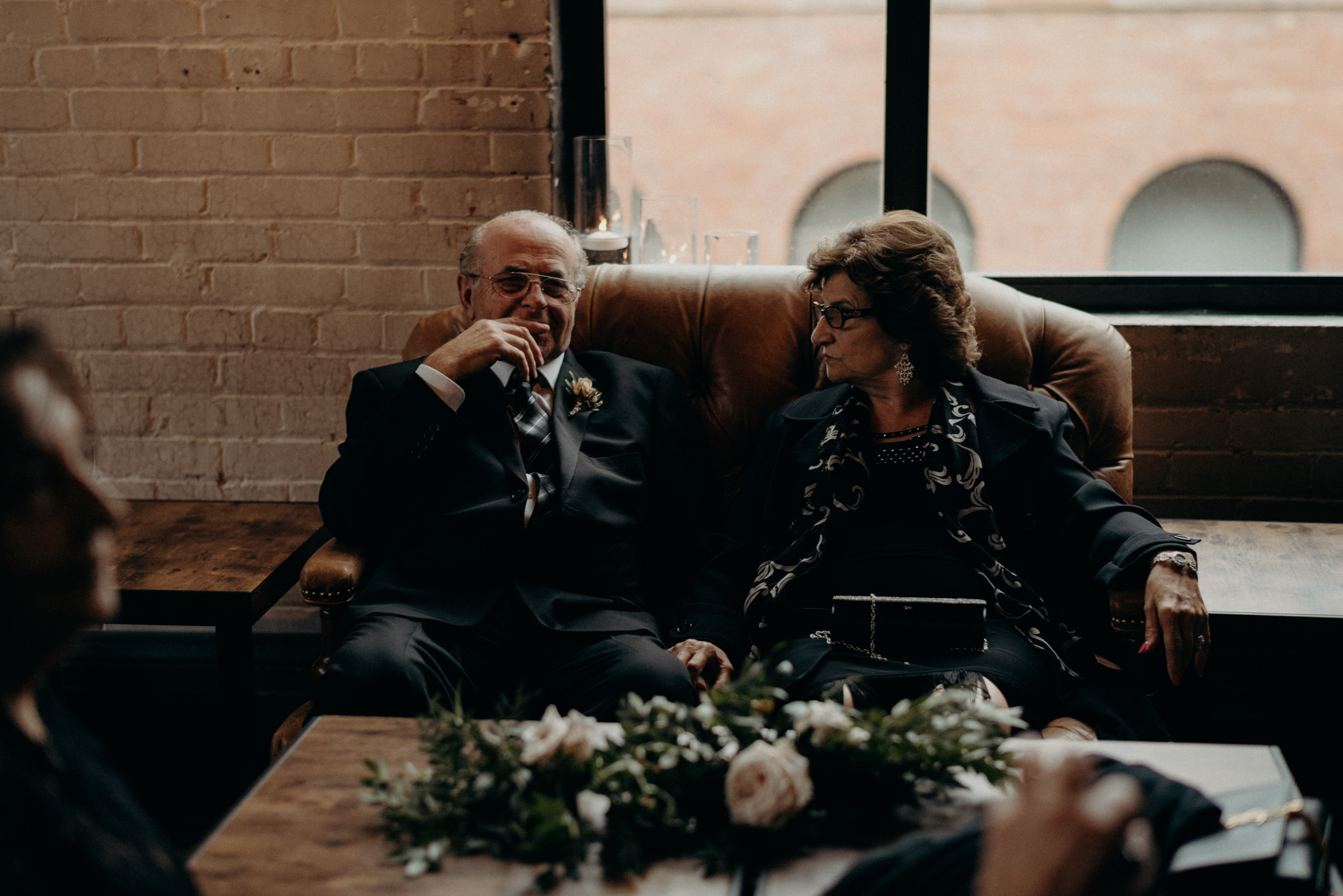 grandparents of bride sitting on couch during cocktail hour