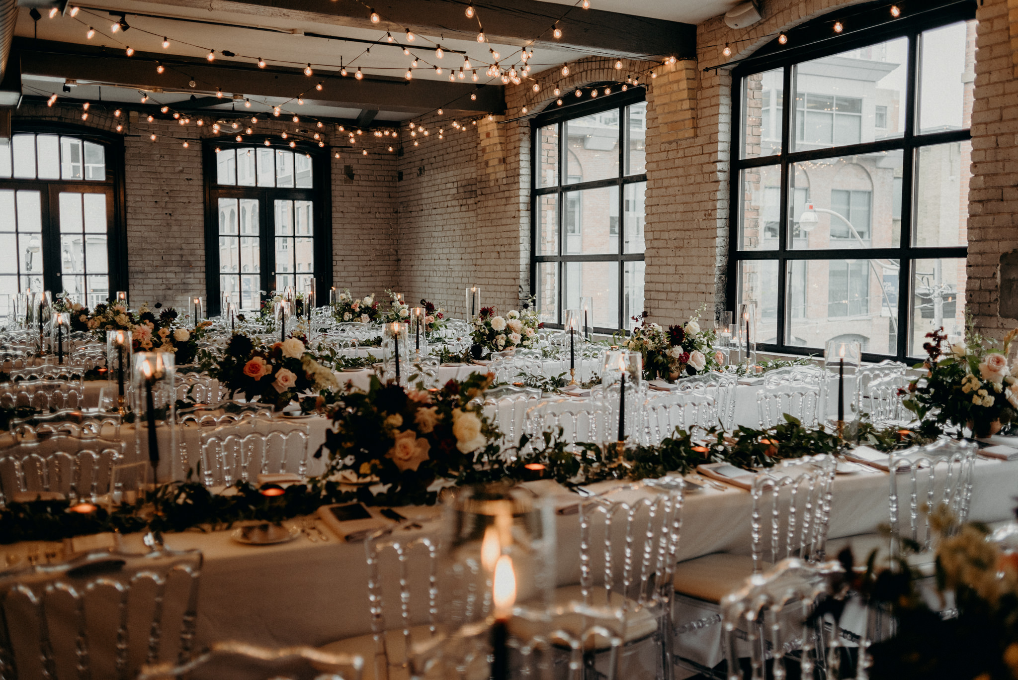 Romantic Storys Building wedding reception setup with string lights and candles on table