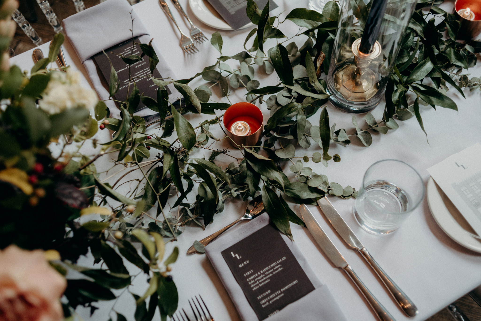 Greenery and candles on table, Storys Building wedding reception
