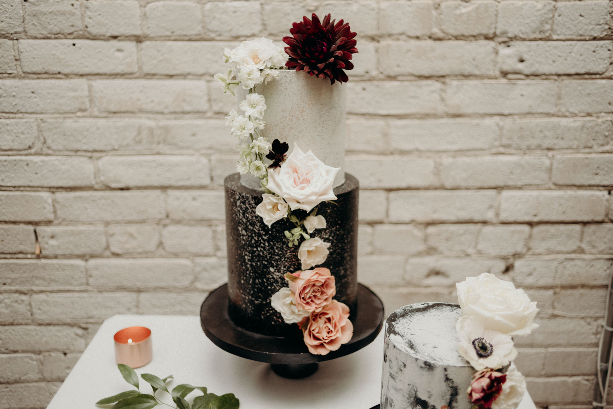White and black tiered cake with lots of fresh flowers