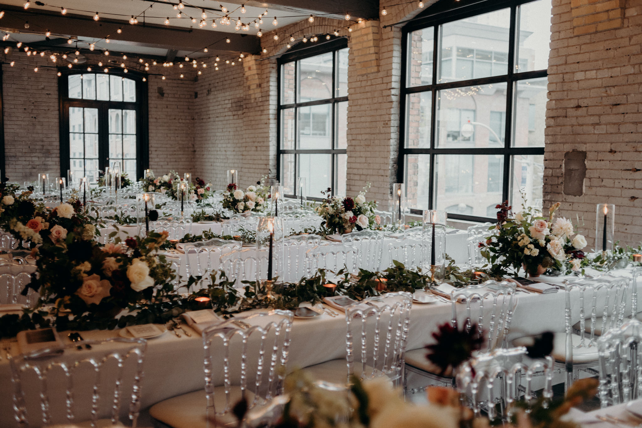 Loft wedding reception with string lights and candles on long harvest tables with lots of flowers