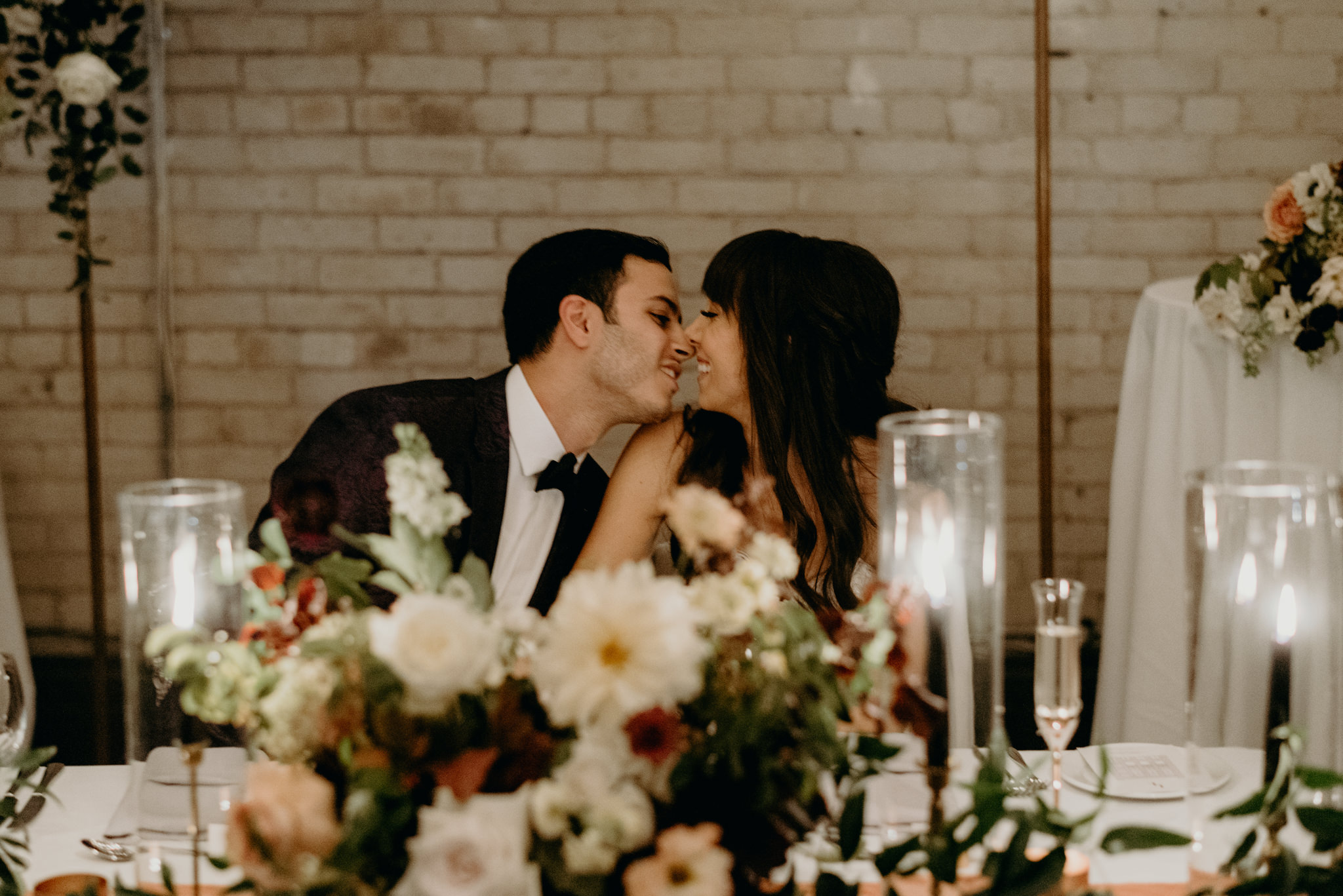 Bride and groom kissing at sweetheart table during reception