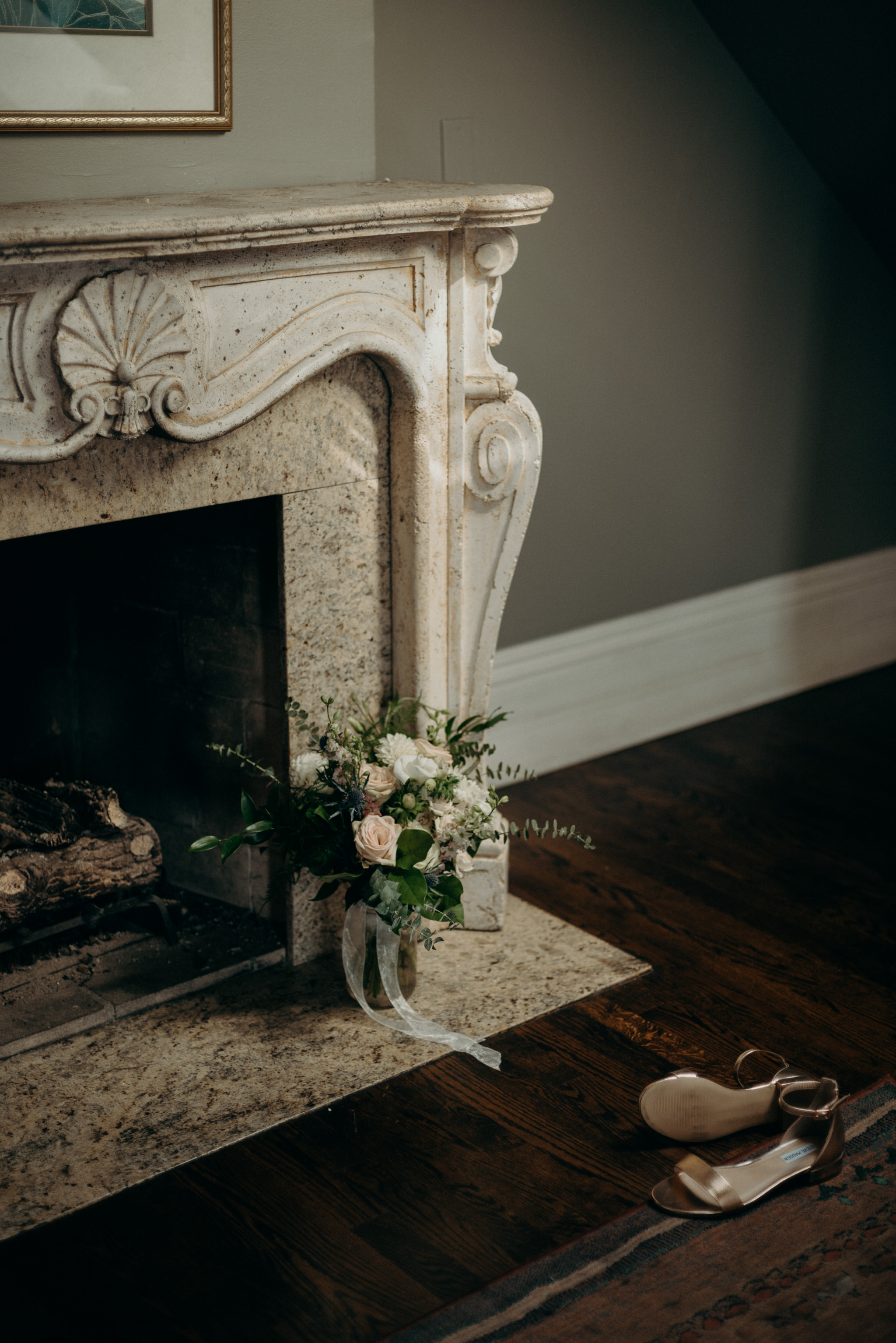 wedding bouquet and shoes on ground in front of elegant vintage fireplace