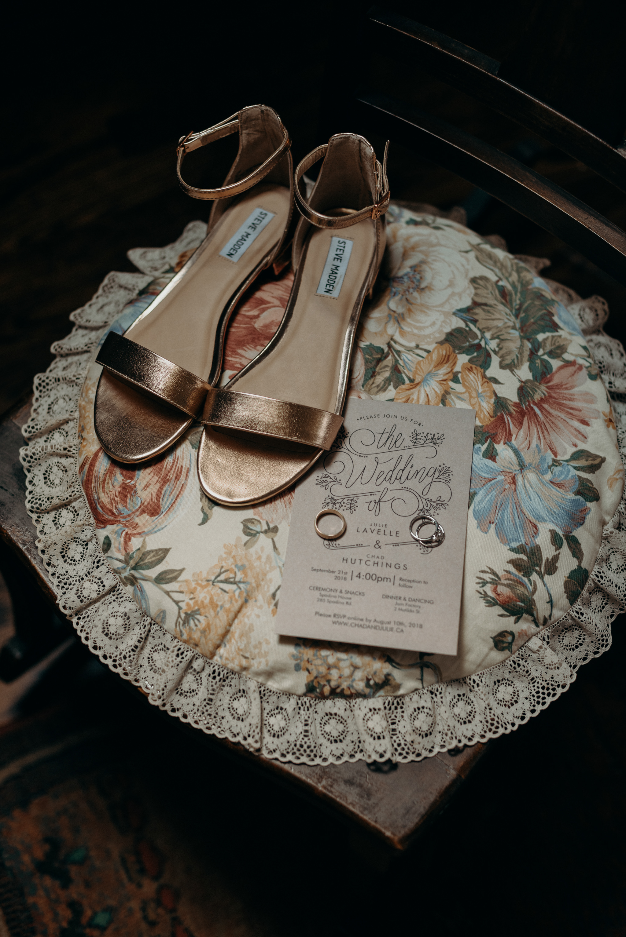 wedding shoes, invitation and rings on round floral pillow