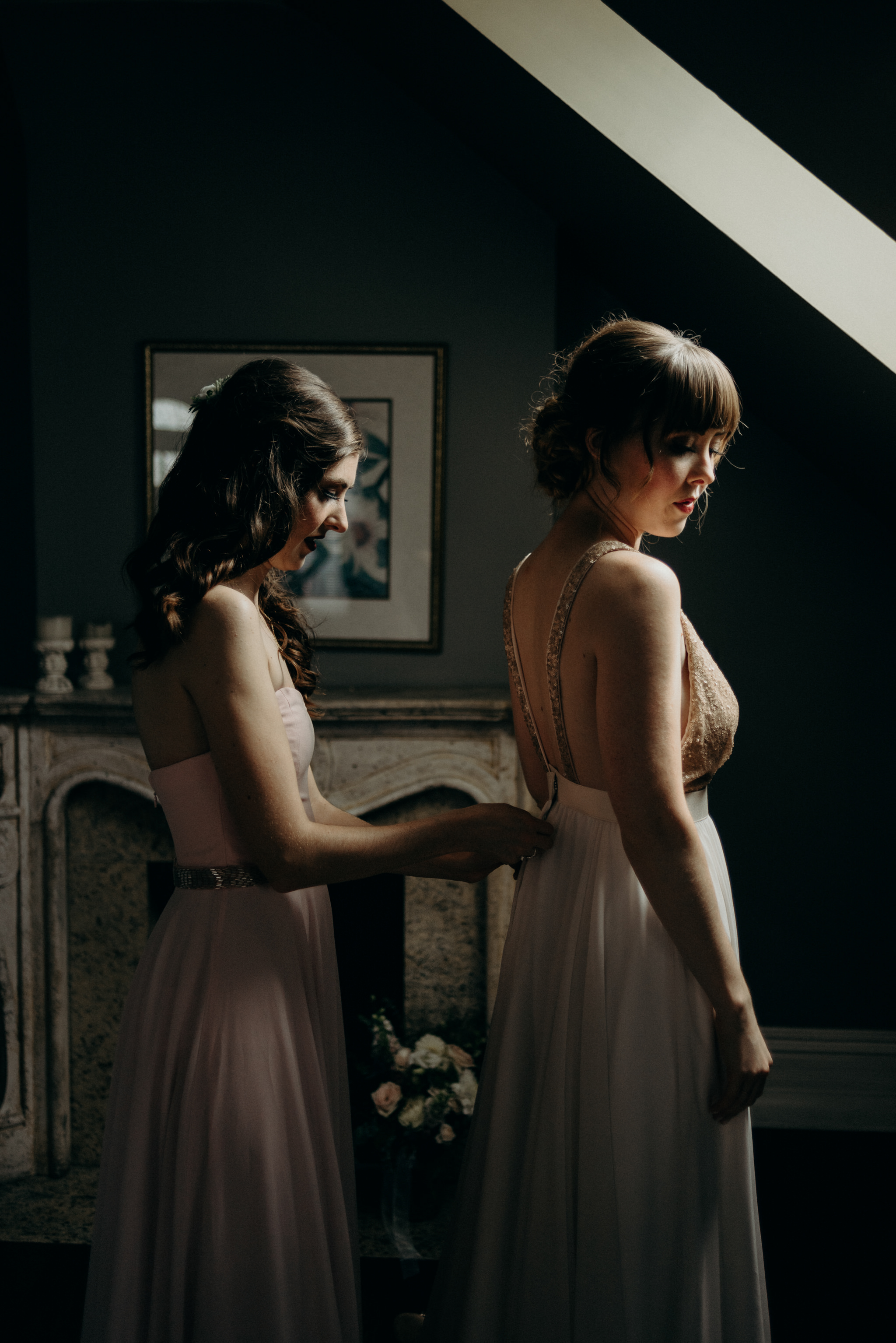 bridesmaid helping bride into dress in attic room with skylight