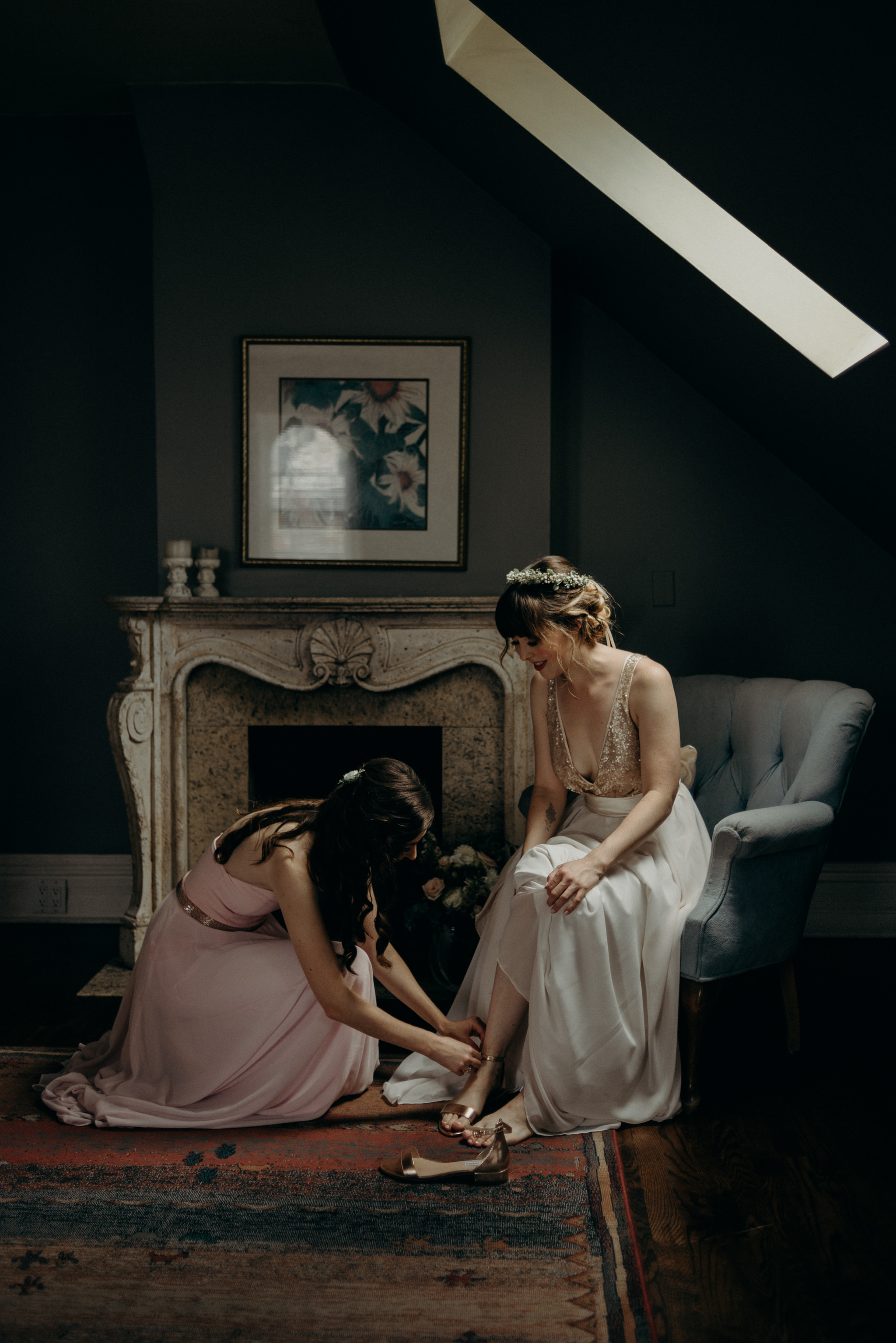 bridesmaid helping bride into shoes as she sits on chair