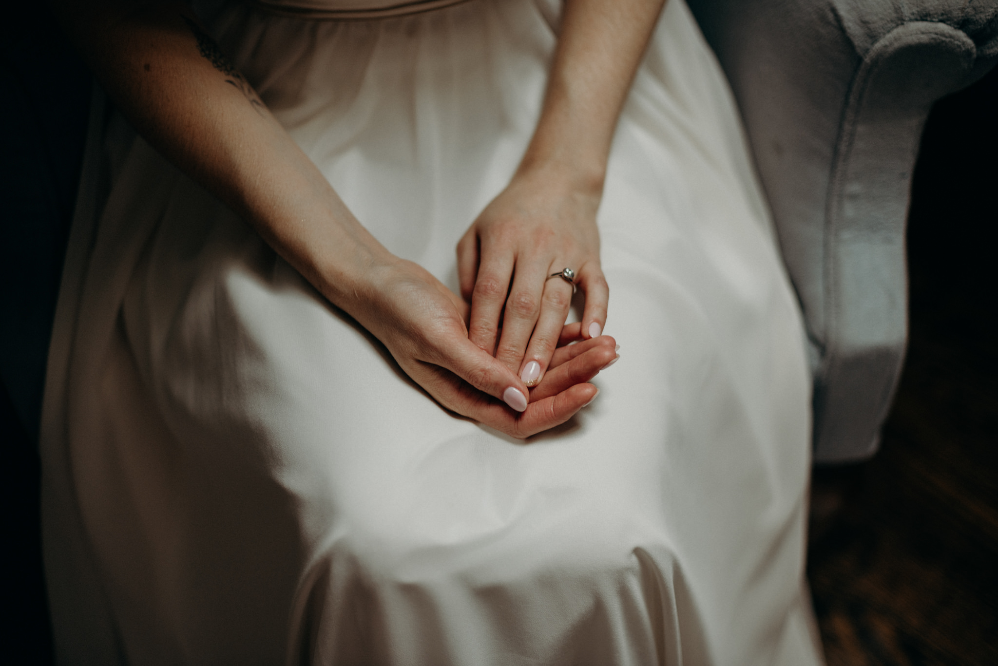 bride in dress, holding hands in lap