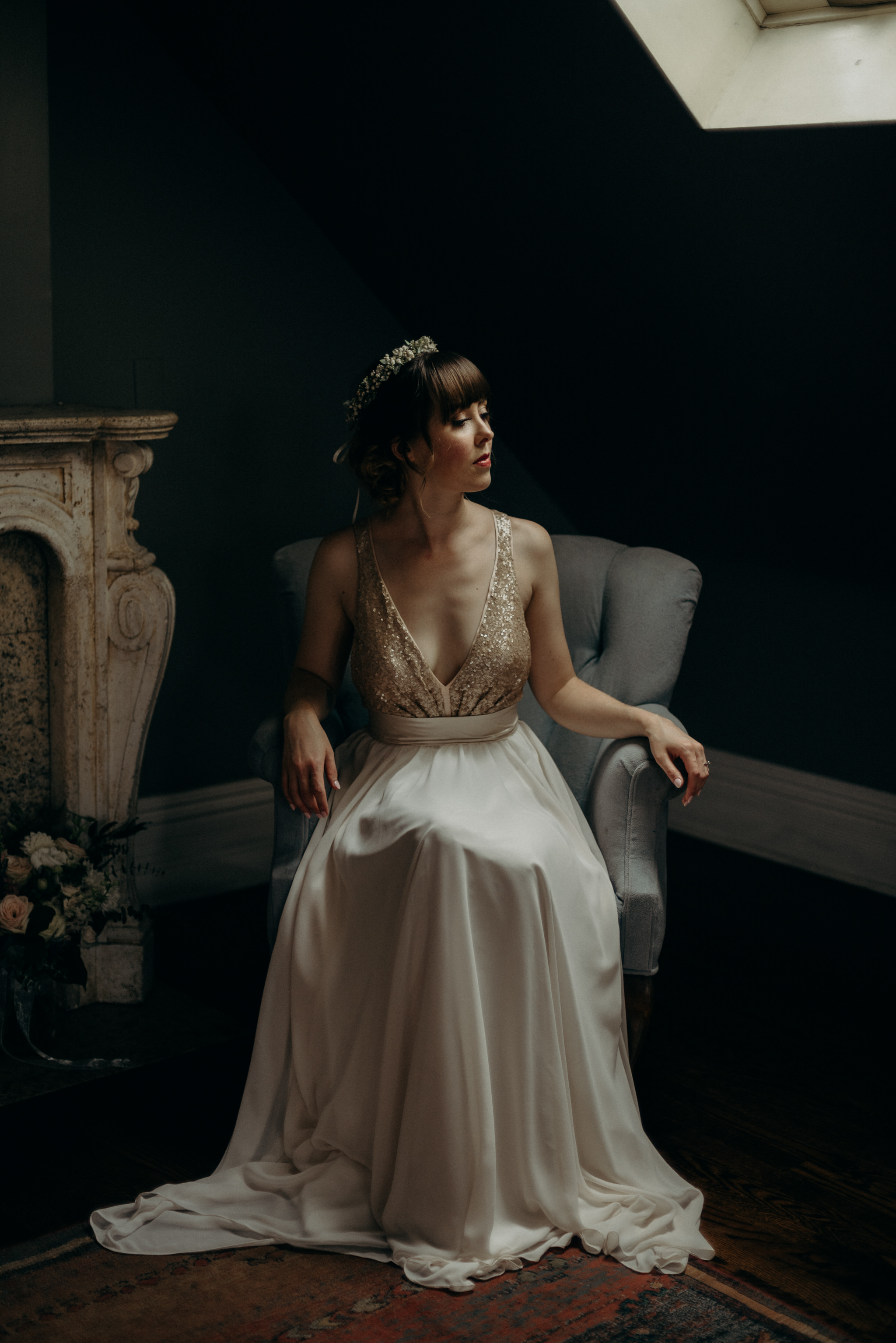 bride sitting in elegant chair in dark room with skylight