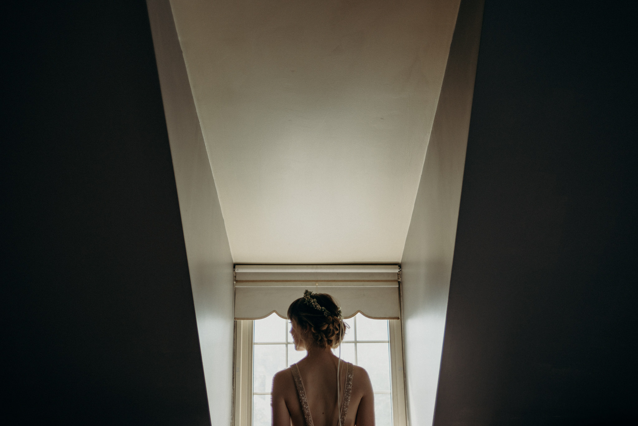 bride looking out window in loft