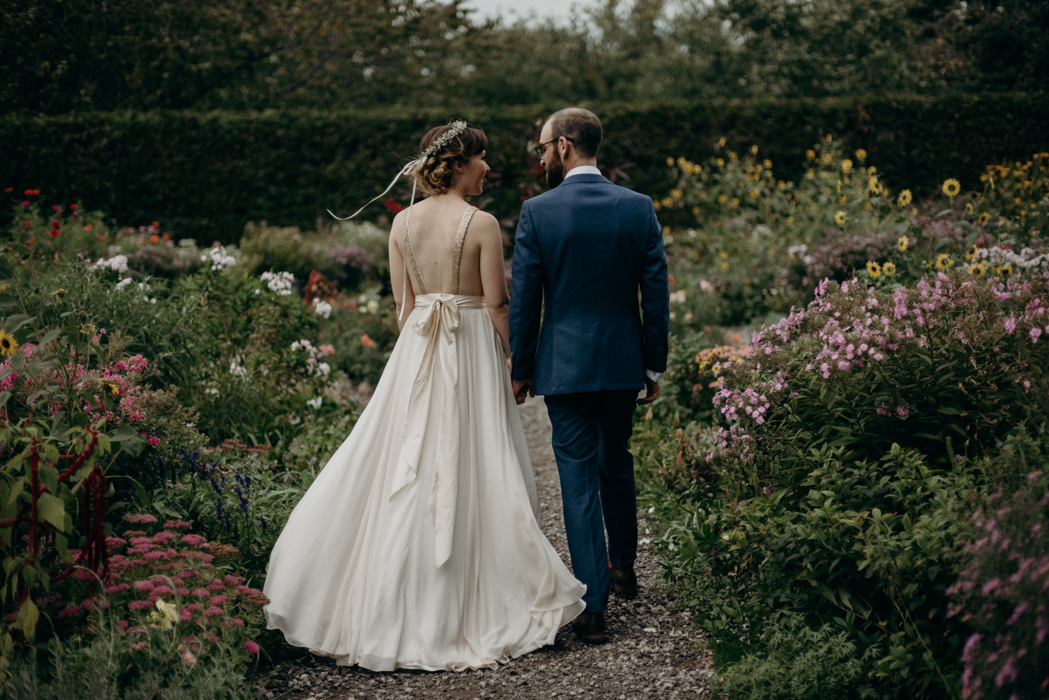 bride and groom walking in flower gardens