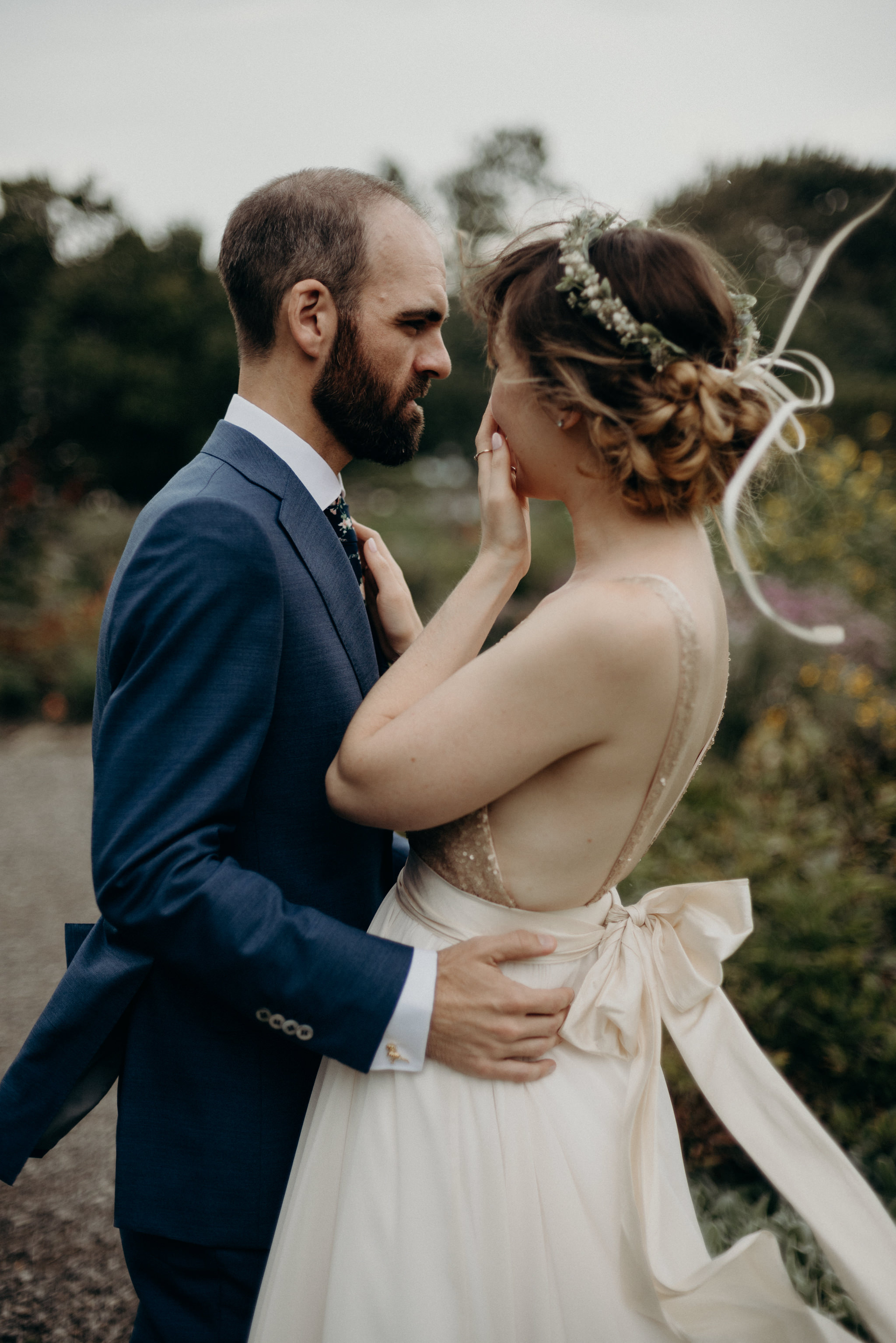 bride hugging groom in gardens on a windy day