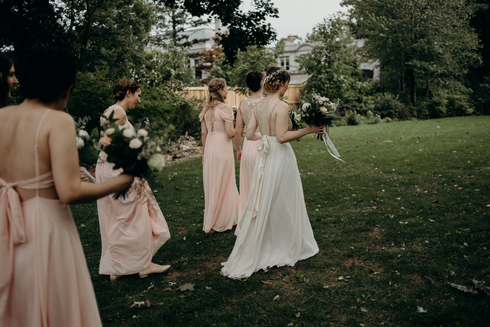 bridesmaids walking on grass at Spadina Museum