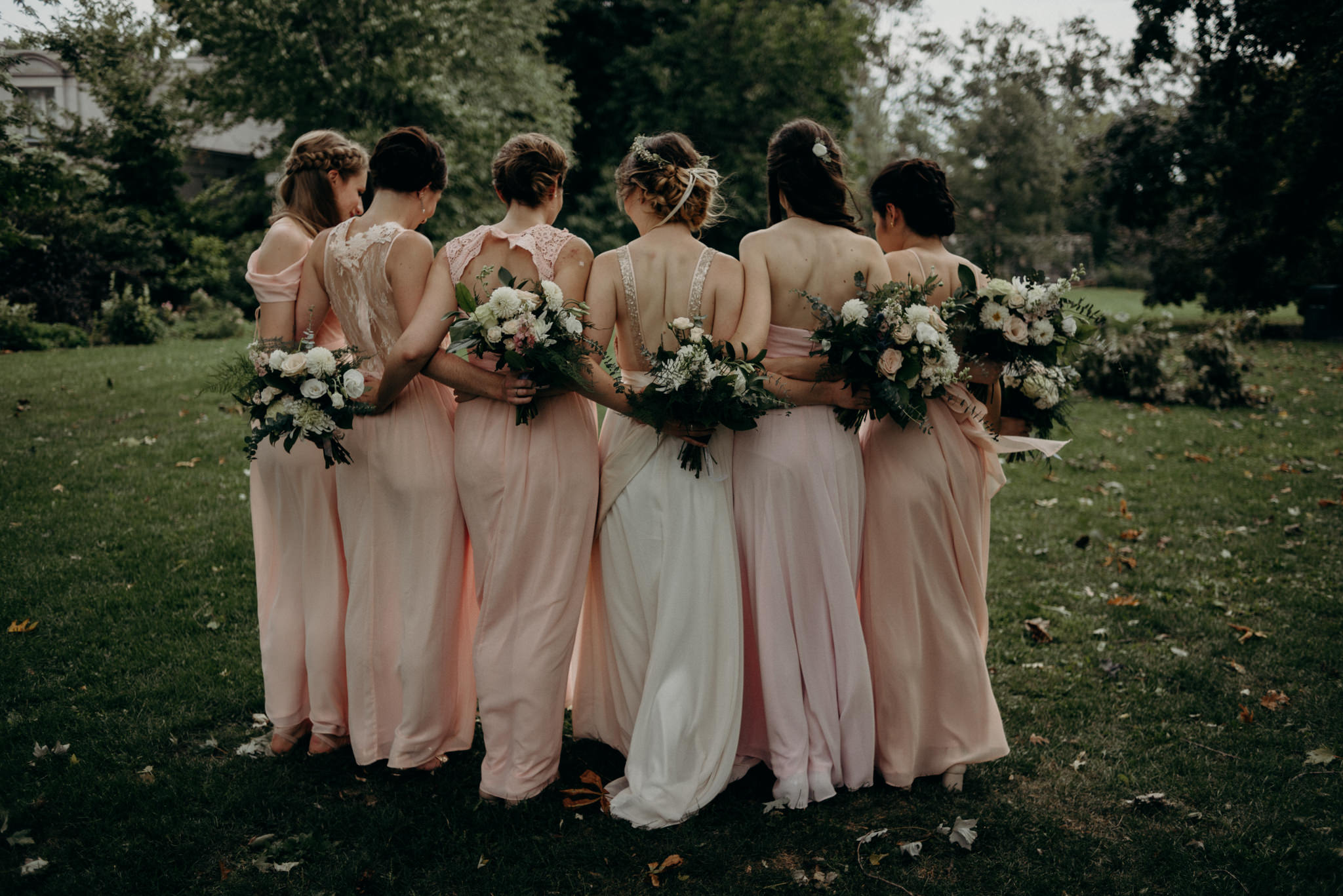 bridesmaids hugging outside