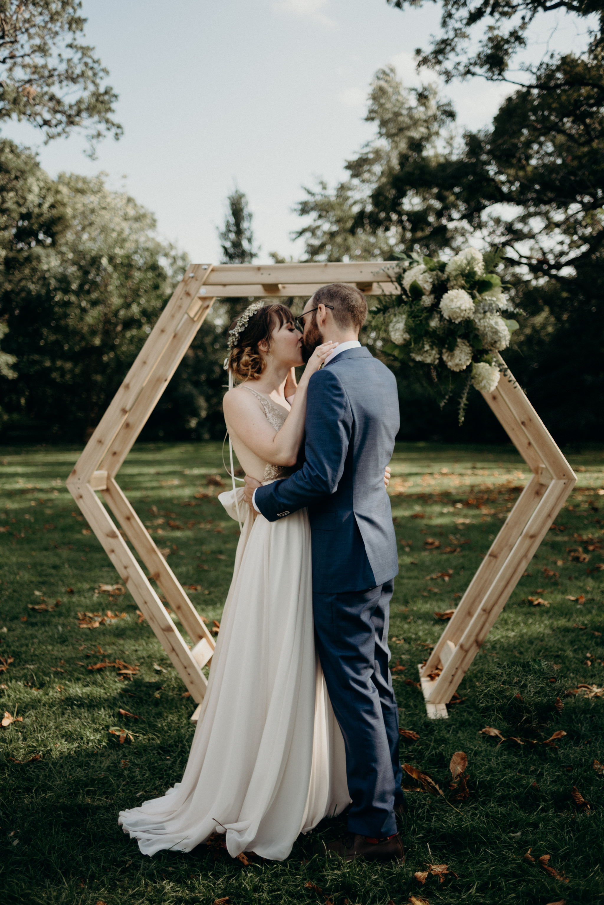 first kiss in front of wood hexagon backdrop during outdoor ceremony