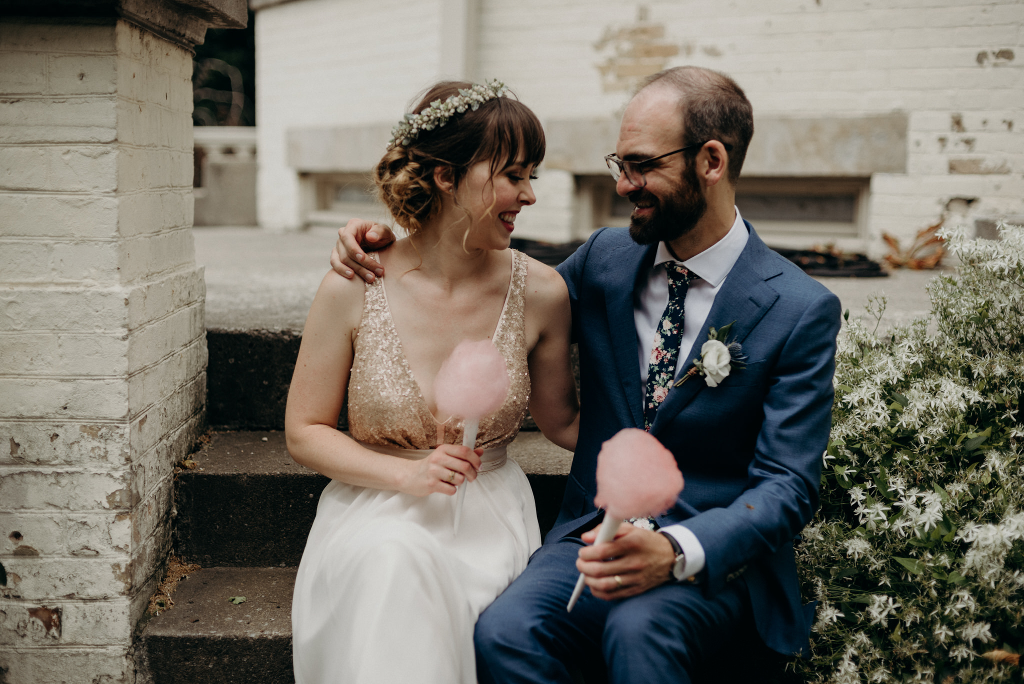 bride and groom sitting on steps of Spadina Museum with cotton candy