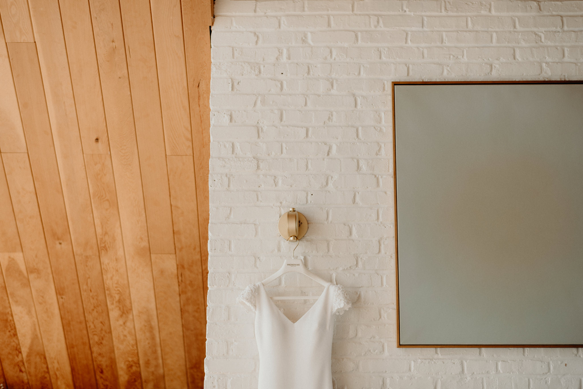 Pronovias wedding dressing hanging on white brick wall