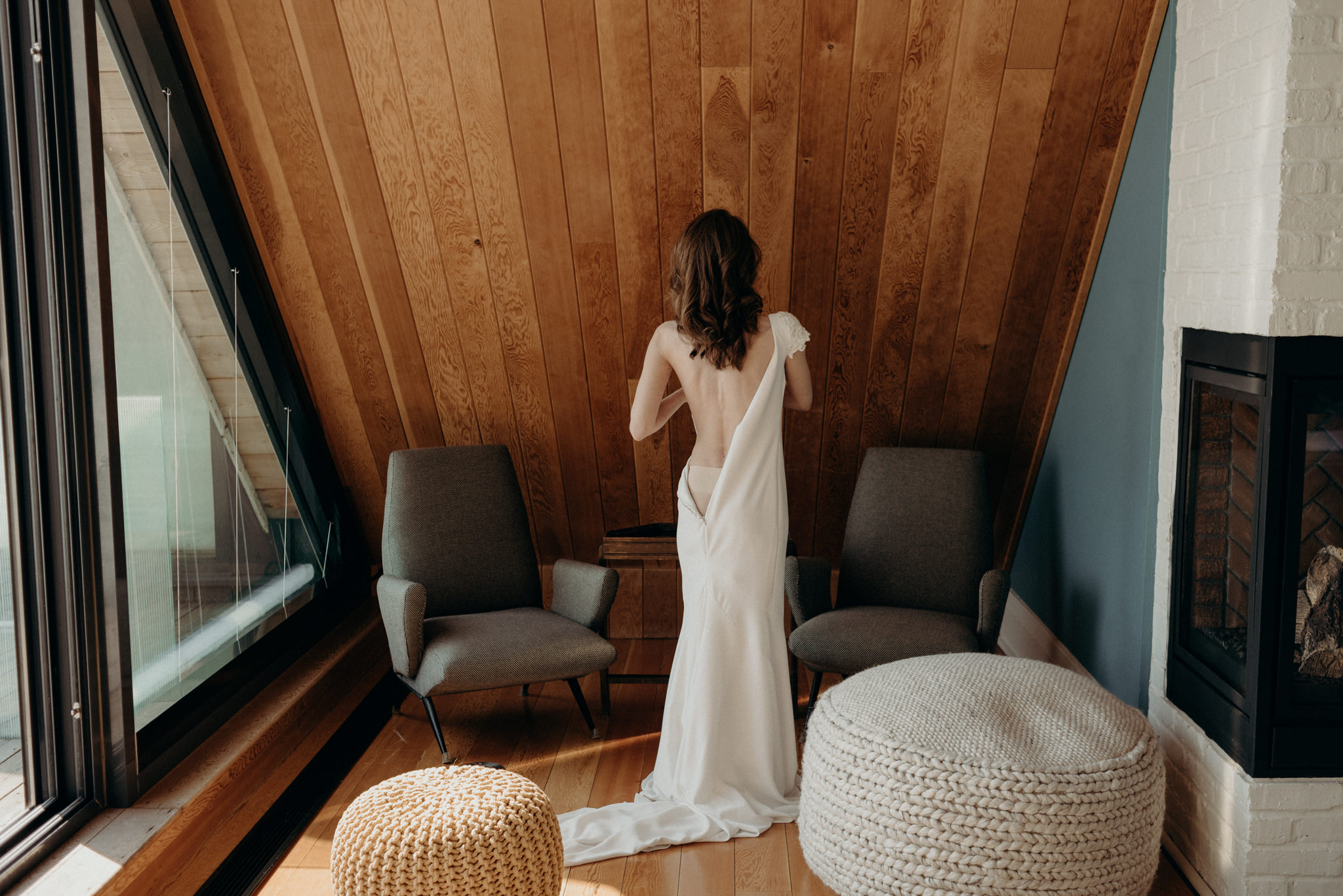 bride getting into dress in a-frame cabin room with large windows