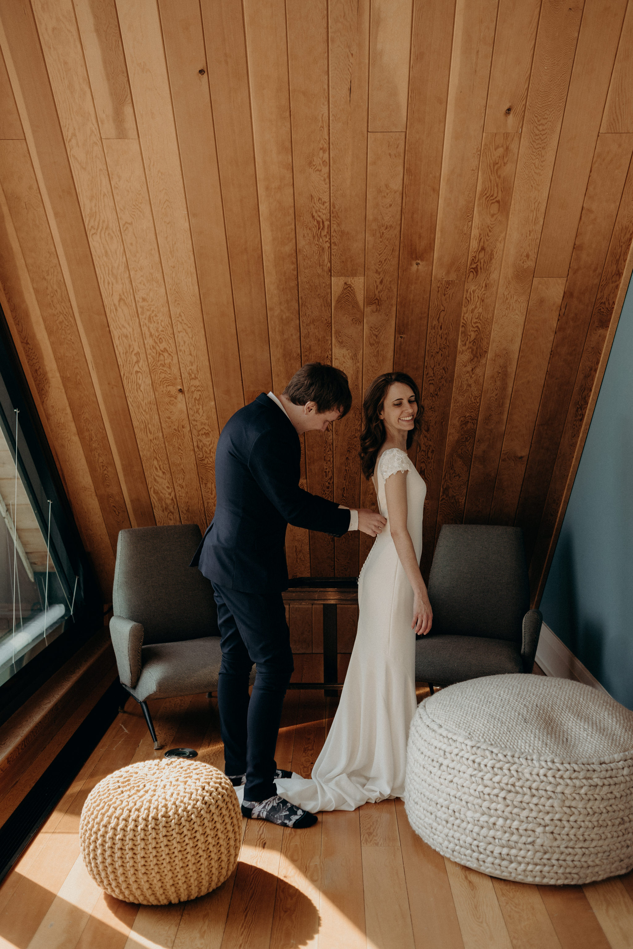 groom helping bride get into dress