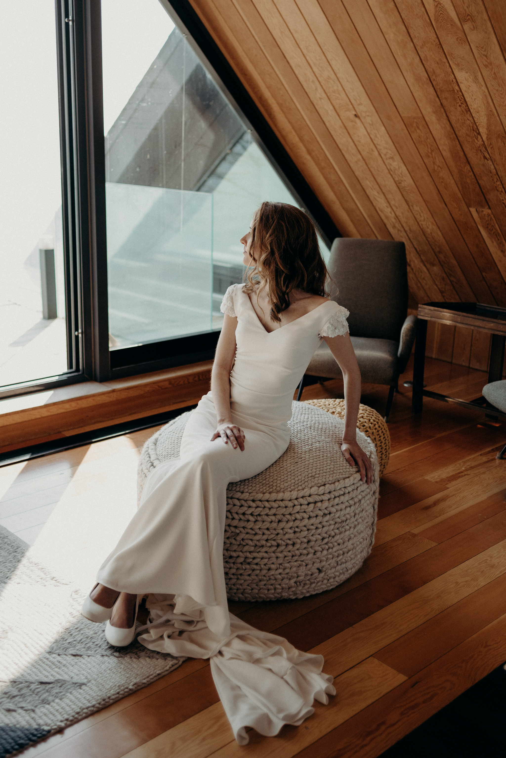 Bride sitting on pouf looking out window