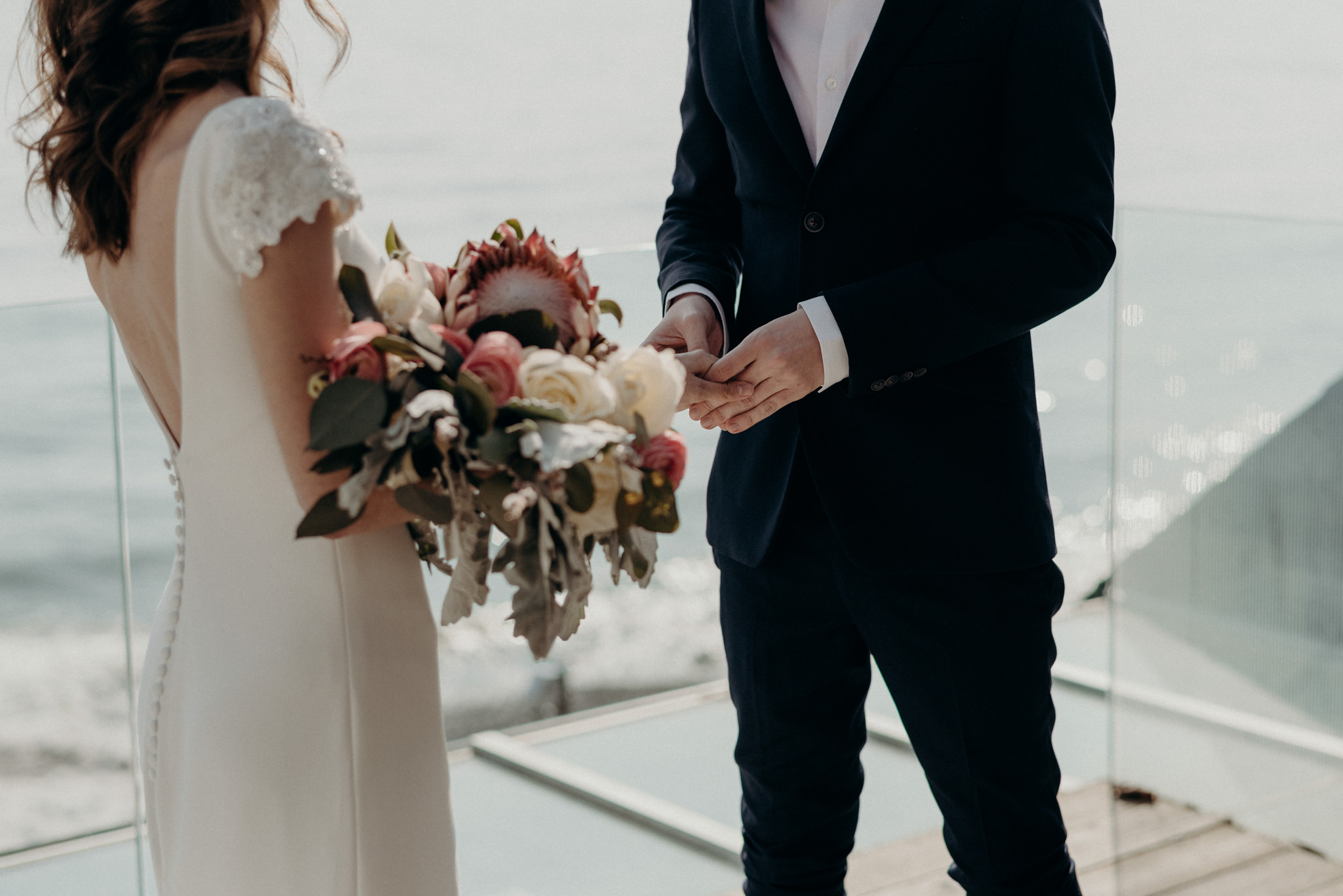 groom holding brides hand during outdoor winter wedding ceremony