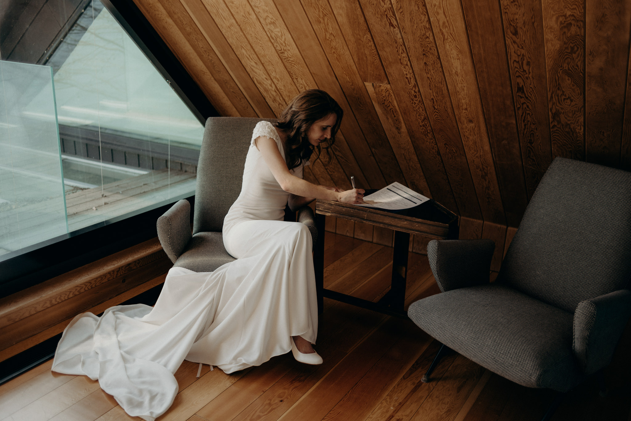 bride signing marriage license inside a-frame cabin